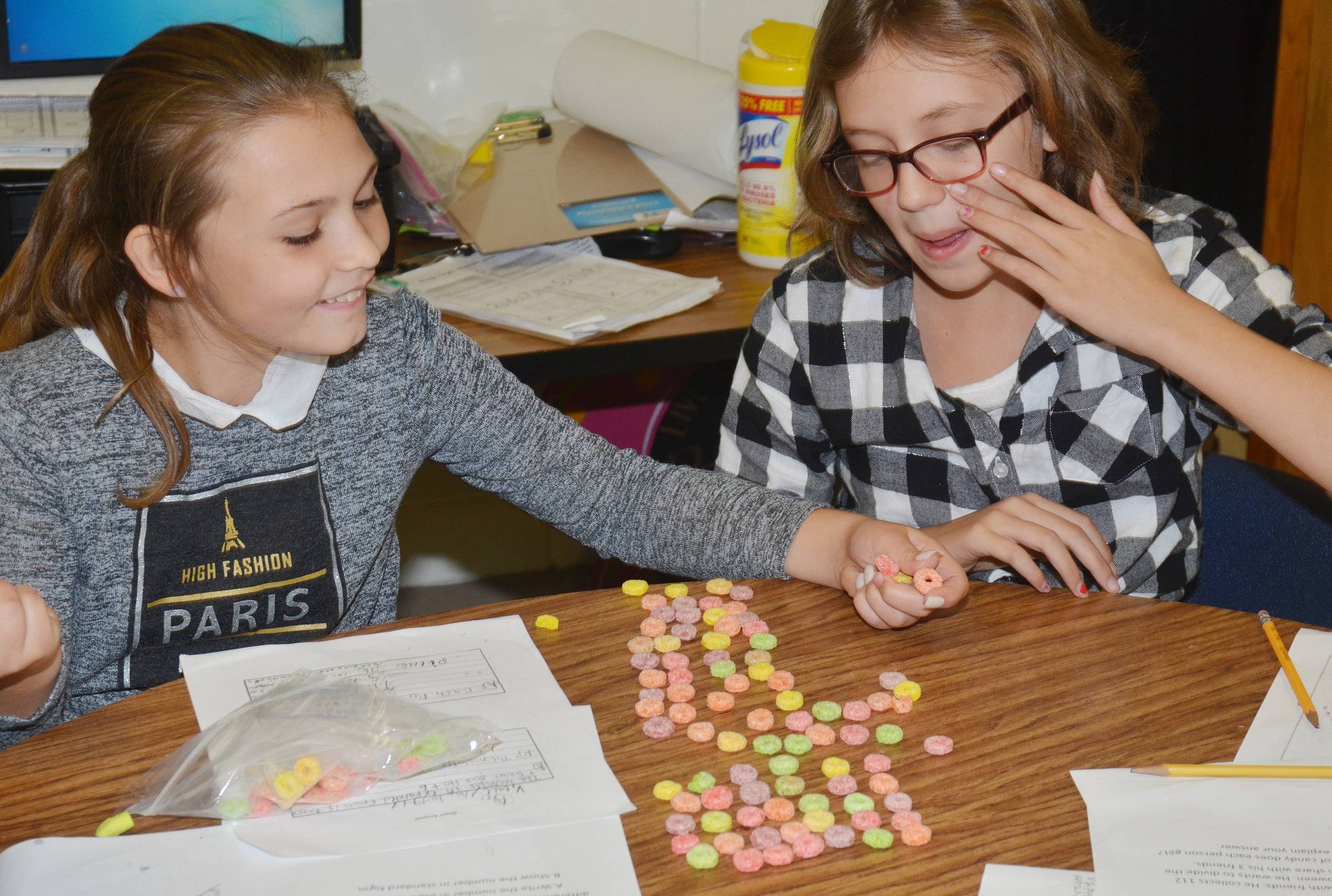 CES fourth-graders Kealey Mann, at left, and Trinity McFarland count using pieces of cereal.
