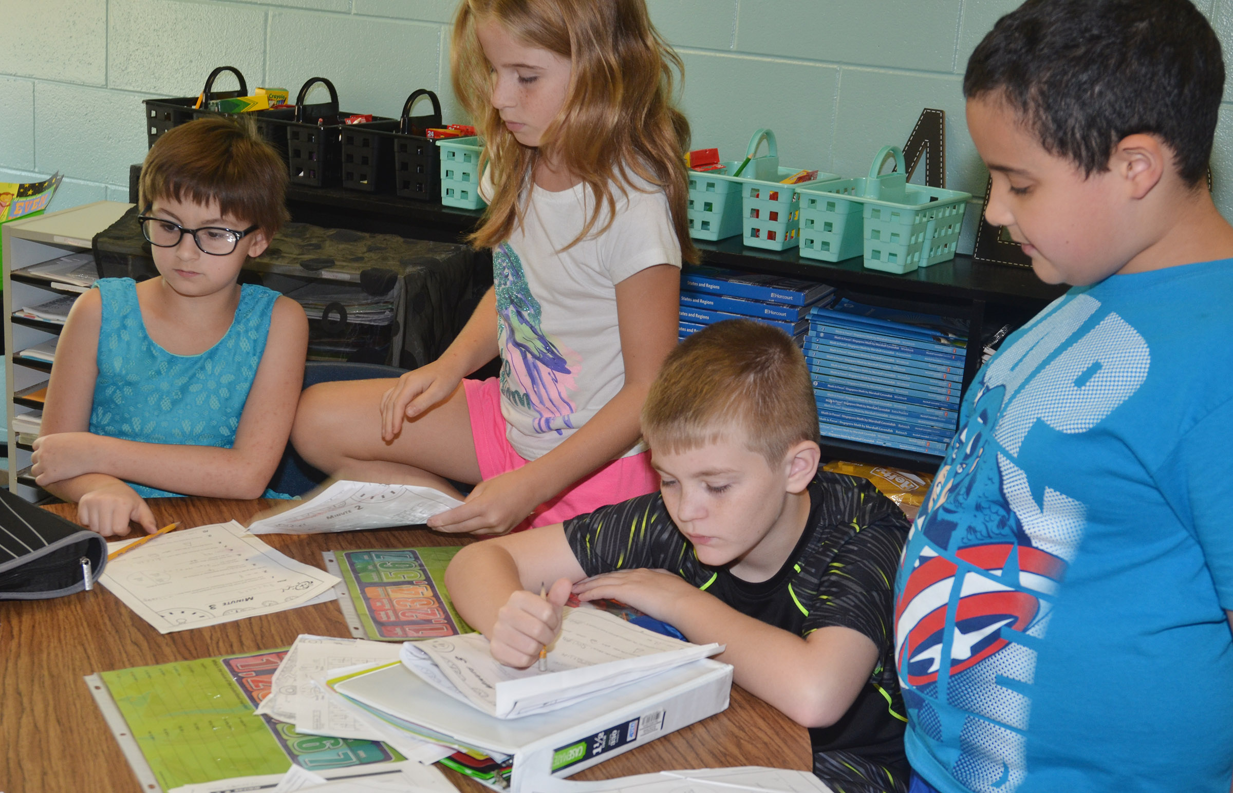 CES fourth-graders, from left, Raeanna Jefferson, Raegan Hayes, Cash Cowan and Tayshaun Hickman work on place value worksheets.