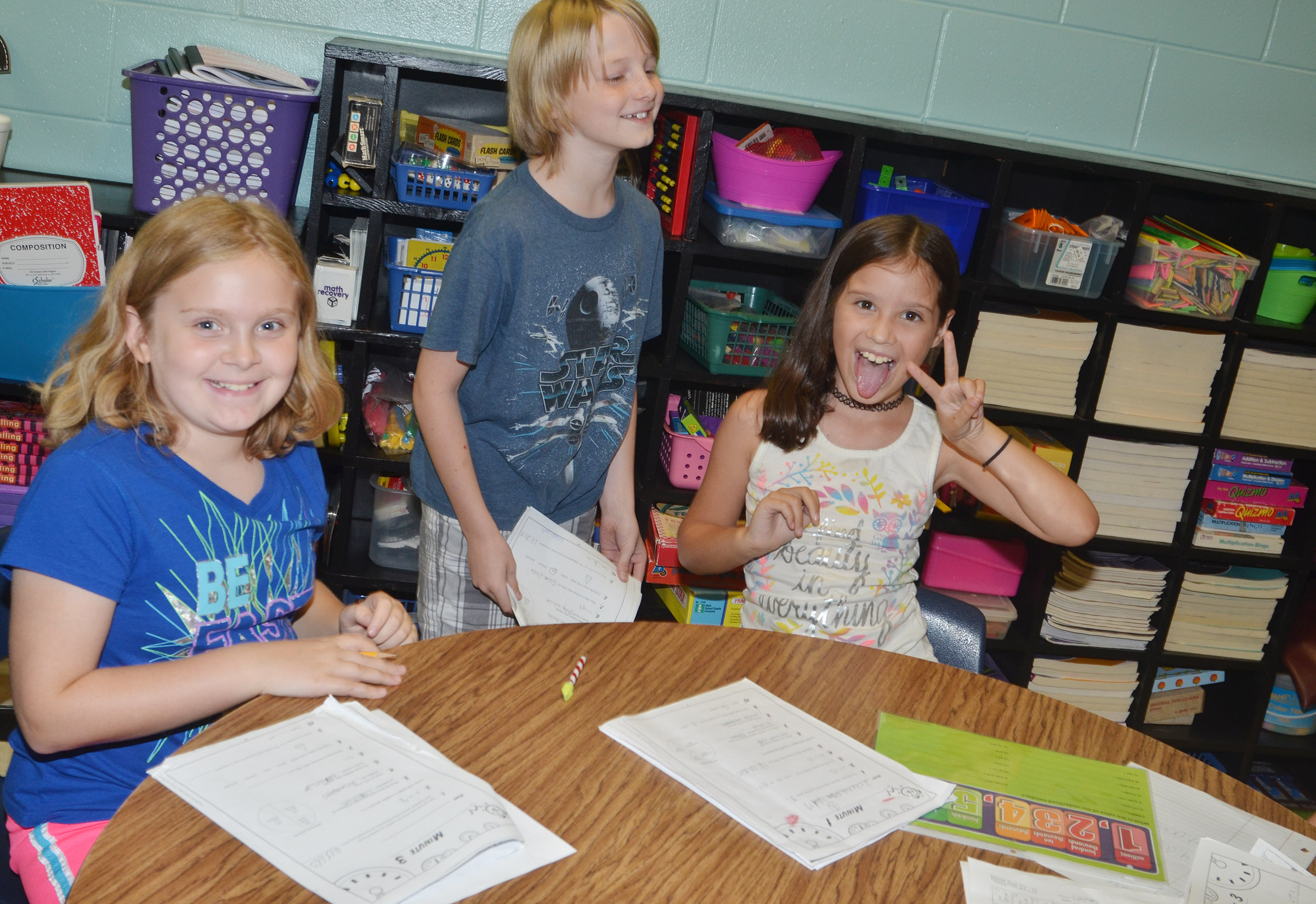 From left, CES fourth-graders Arianna Childers, Devin Underwood and Zehavah Negron have fun while working on their place value worksheets.