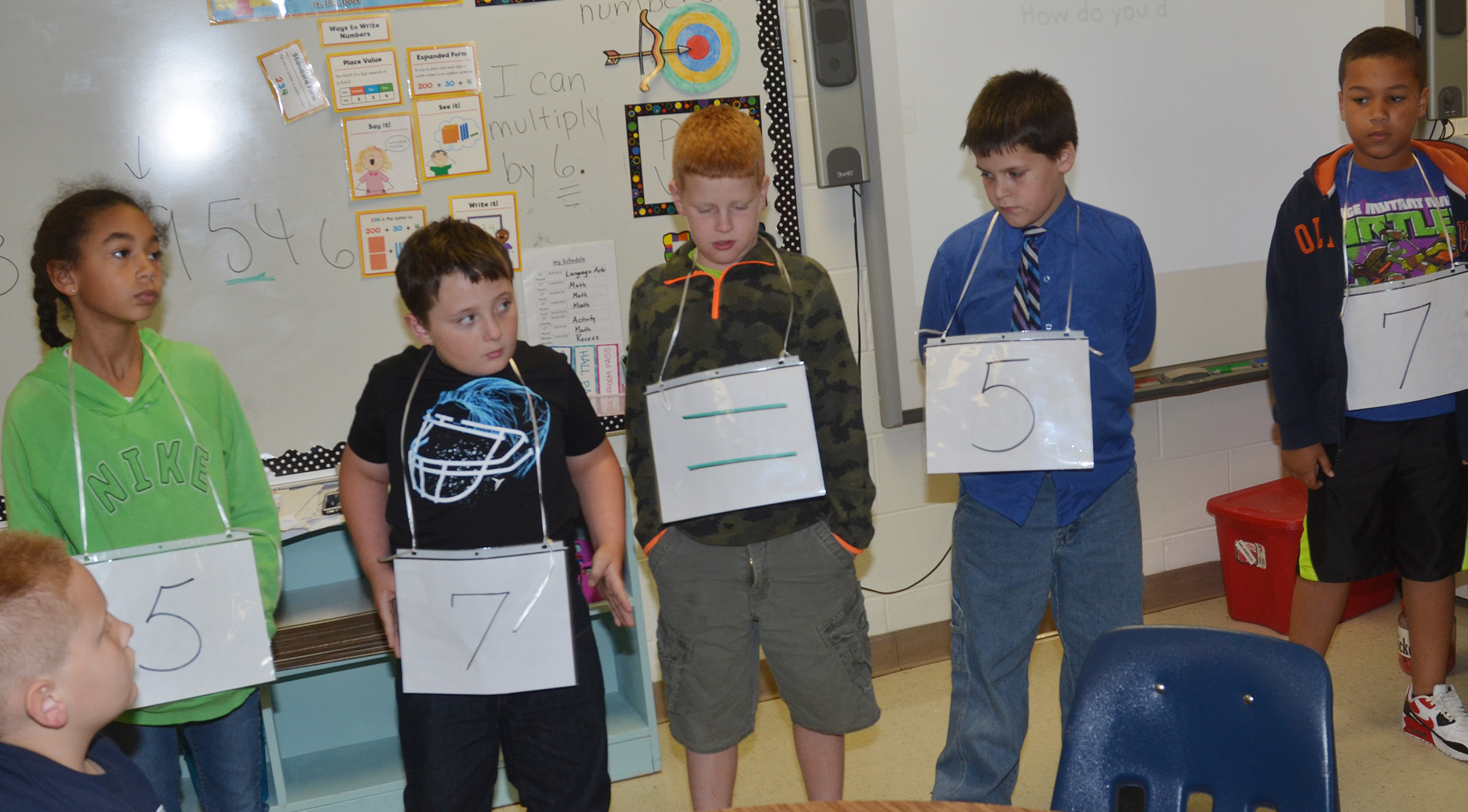 From left, CES fourth-graders De'Asia Fisher, J.J. Scharbrough, Westin Dudgeon, Chris Brown and Zarek Stone create equal numbers.