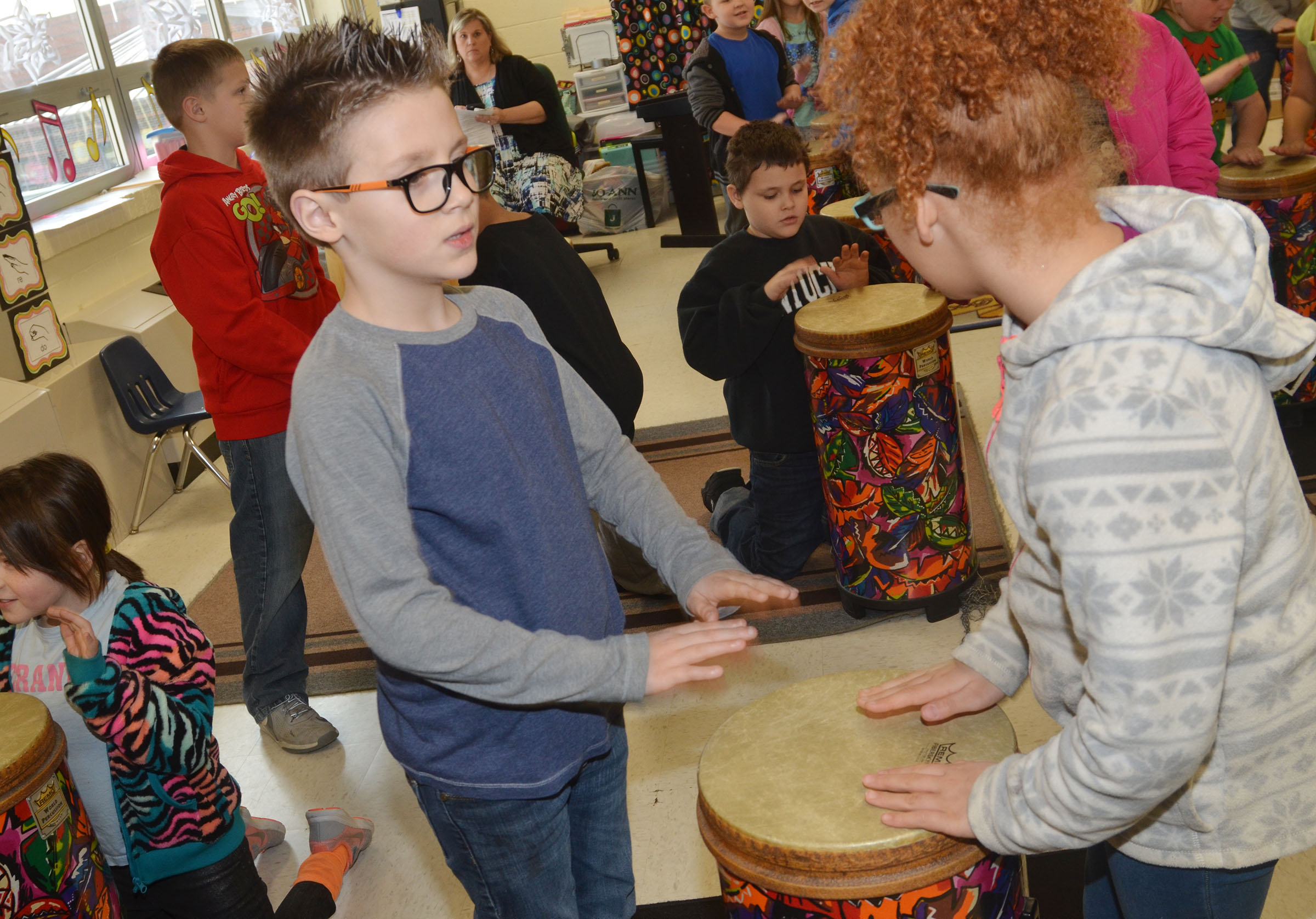CES second-graders Dalton Shively, at left, and Kallie Taylor practice rhythms on the drums.