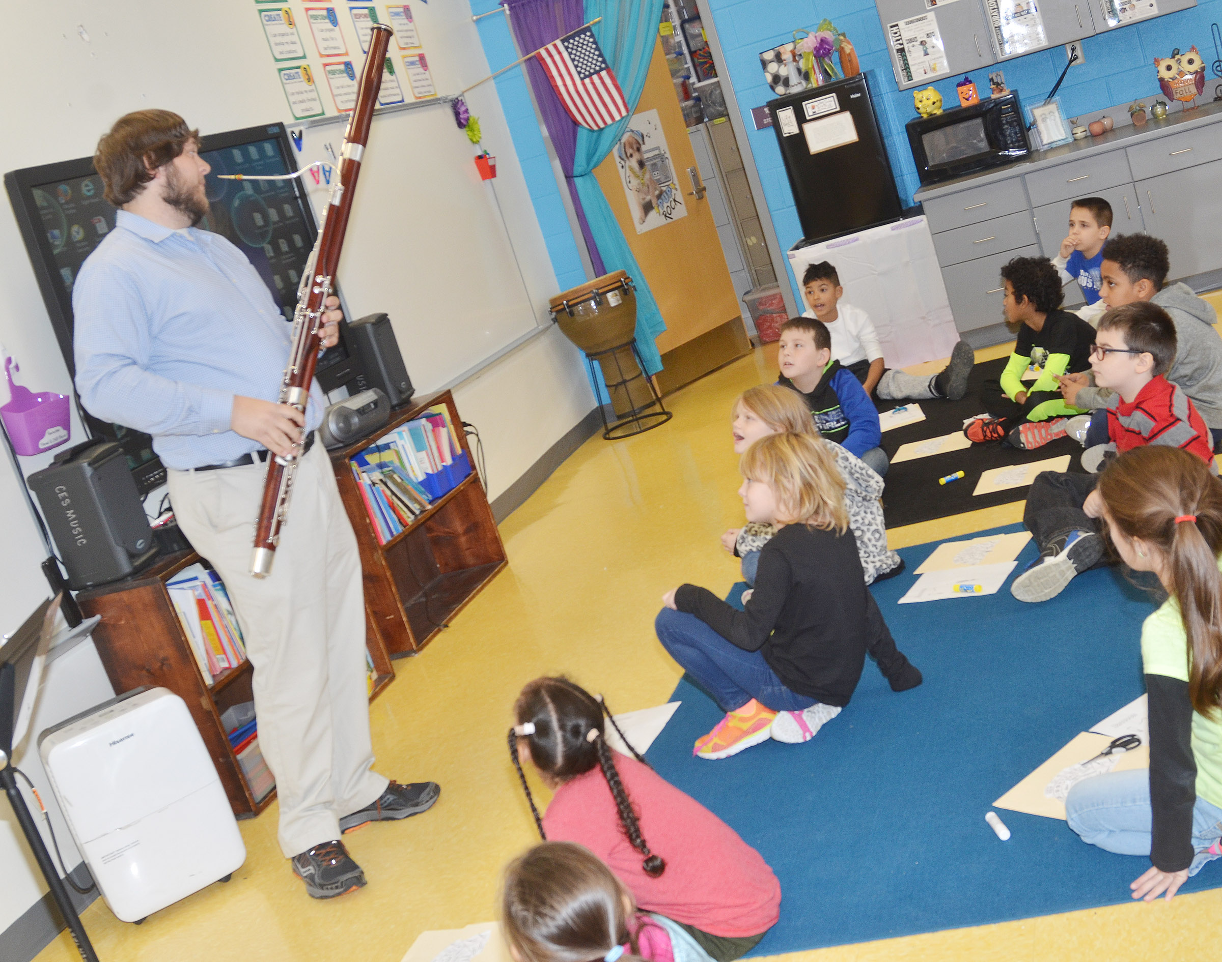 Campbellsville University education student Scott Caffee shows CES second-graders how to play the bassoon.