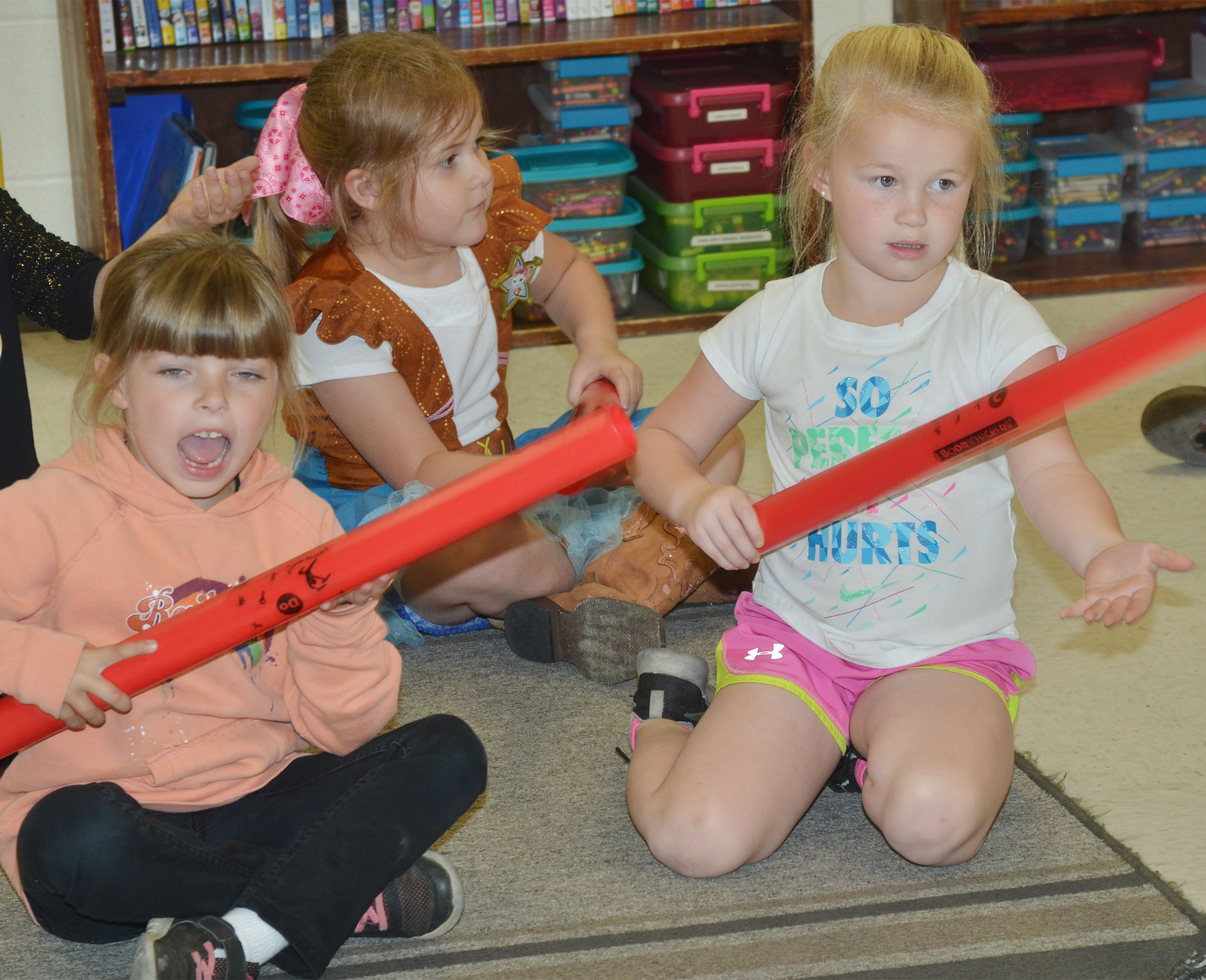 CES kindergarteners, from left, Madison Wilhoite, Aubrey Knifley and Lillie Judd play the boom whackers.