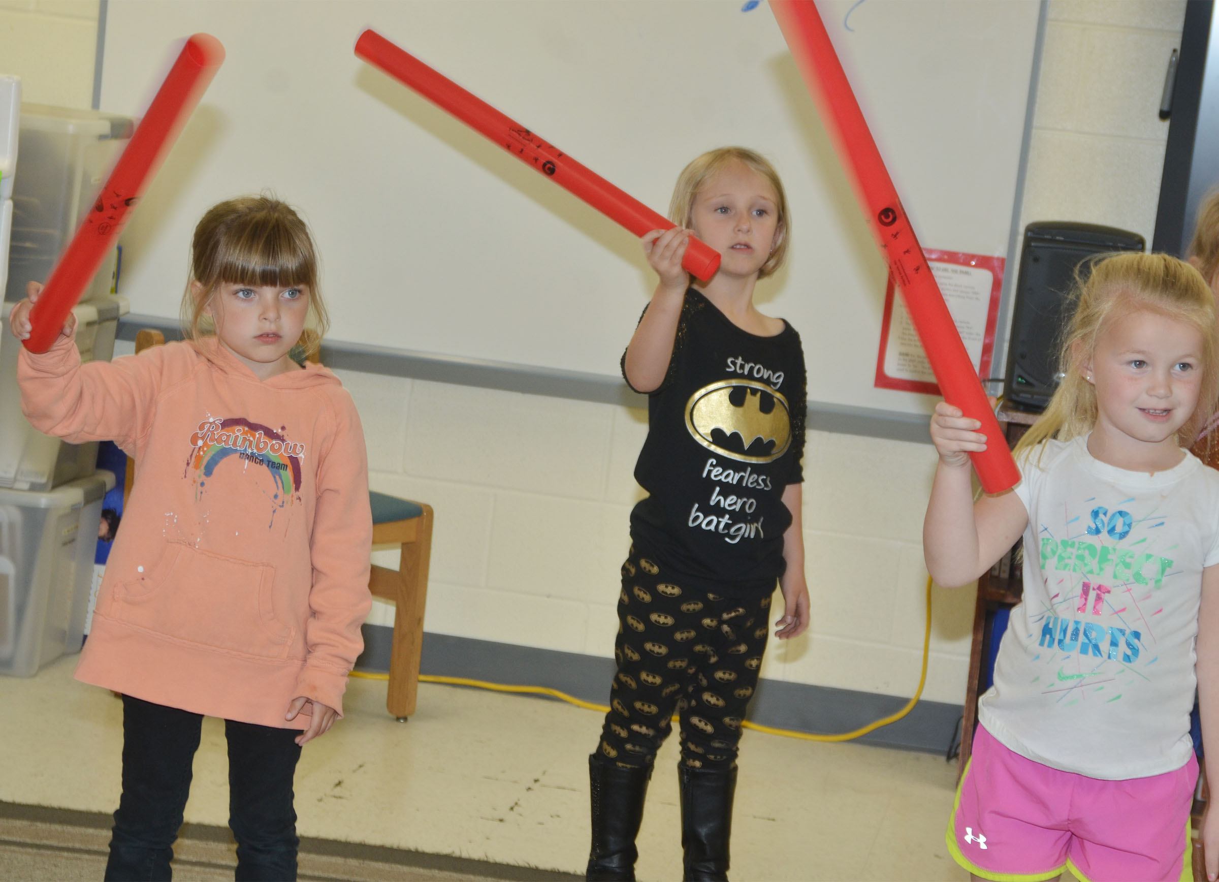 From left, CES kindergarteners Madison Wilhoite, LeeAnna Garvin and Lillie Judd play the boom whackers.