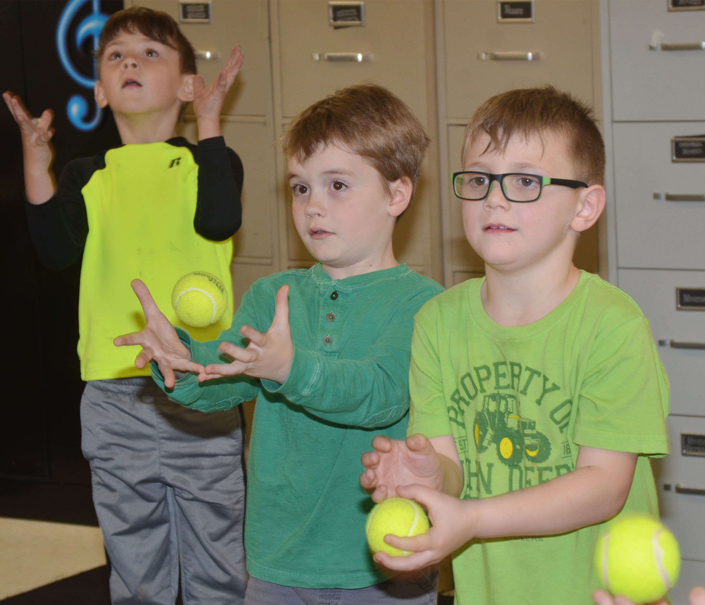 From left, CES kindergarteners Bentley Shively, Gavin Williams and John Lane keep a beat with tennis balls.