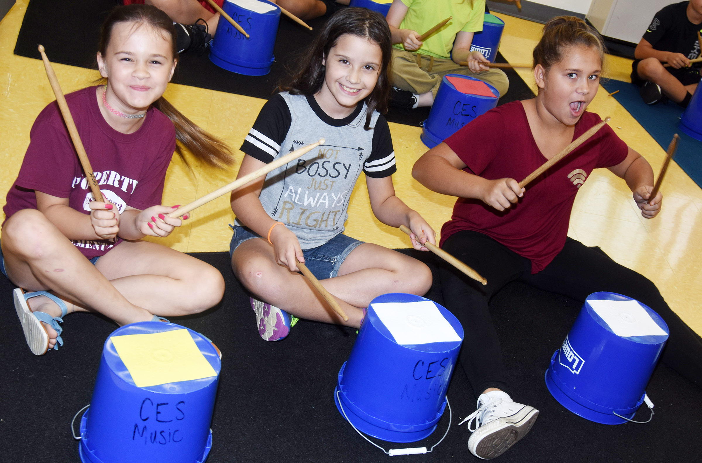 From left, CES fifth-graders Skielei Milby, Zehavah Negron and Emilee Derringer play the bucket drums.