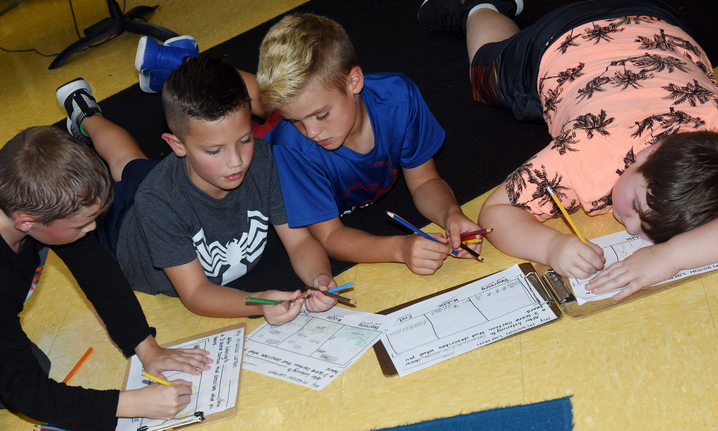 From left, CES third-graders Aiden Forrest, Owen Skaggs, Dax Gray and Luke Mardis draw their cartoons.