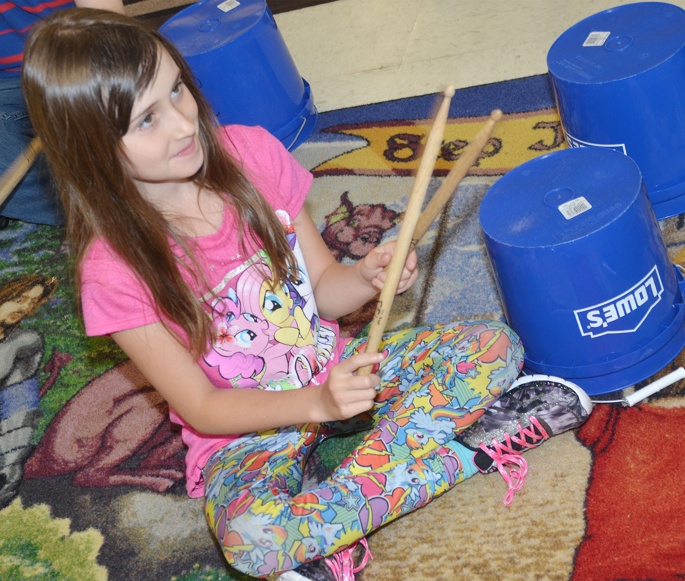 CES second-grader Cadence Burton plays the bucket drums.