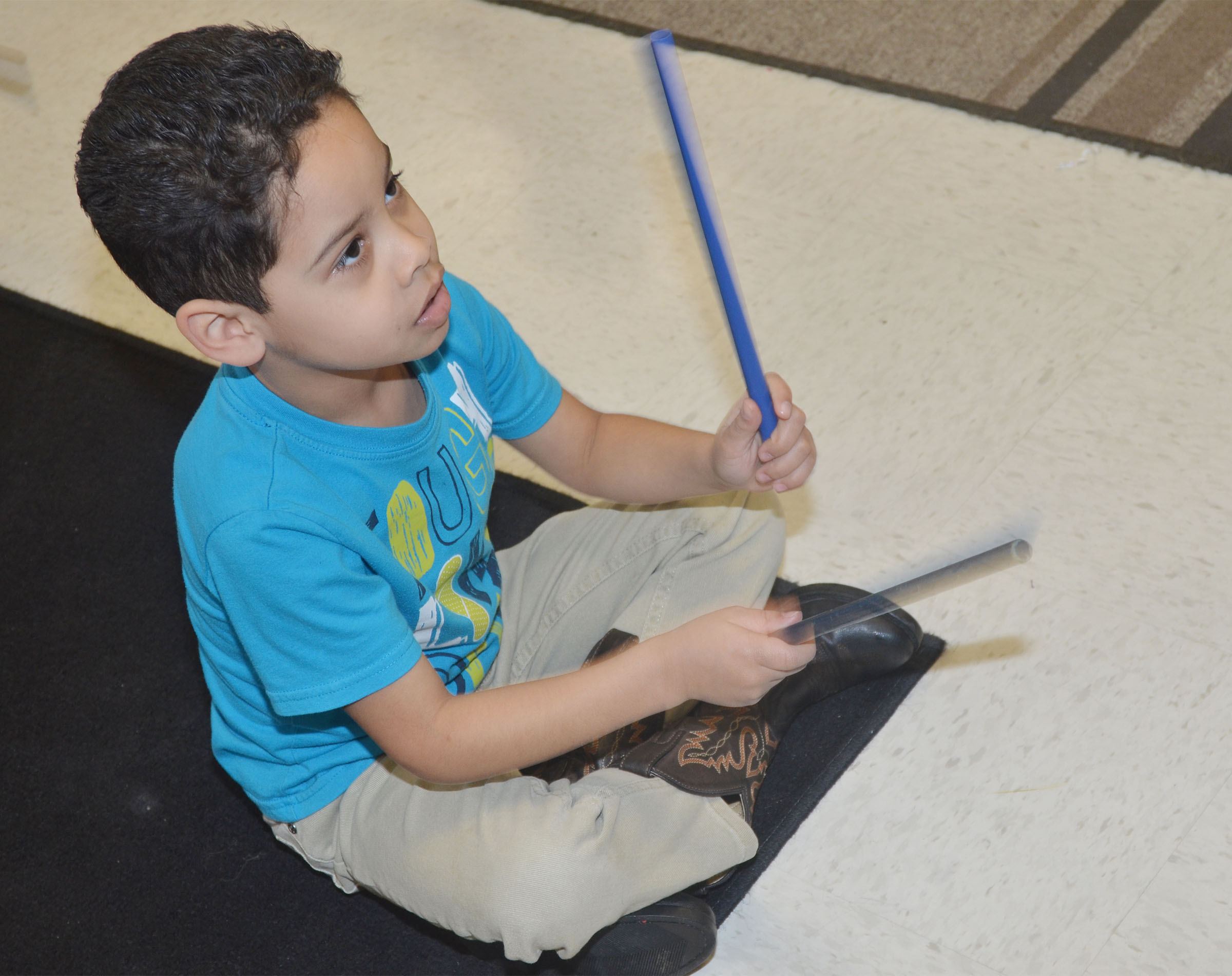 CES kindergartener Demarcus Noyola plays the rhythm sticks.