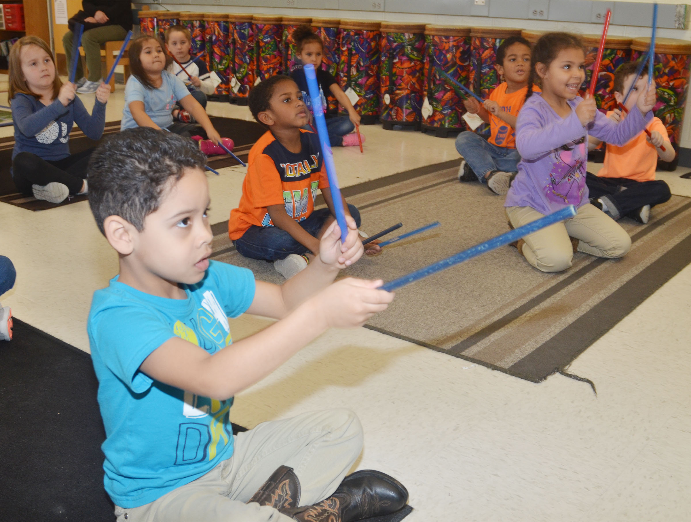 CES kindergartener Demarcus Noyola, at left, plays the rhythm sticks with his classmates.