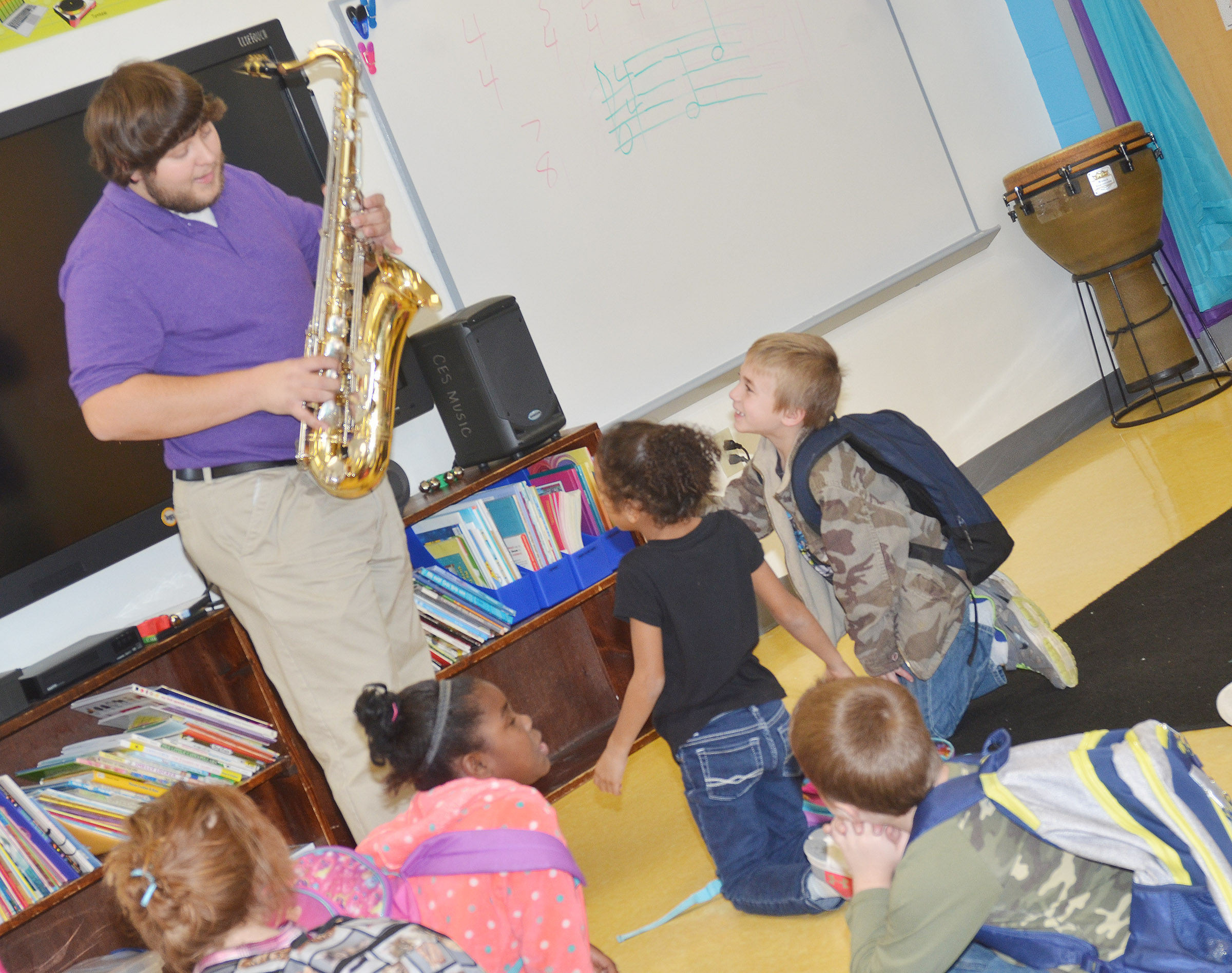 Campbellsville University education student Scott Caffee shows his tenor saxophone to CES first-graders.