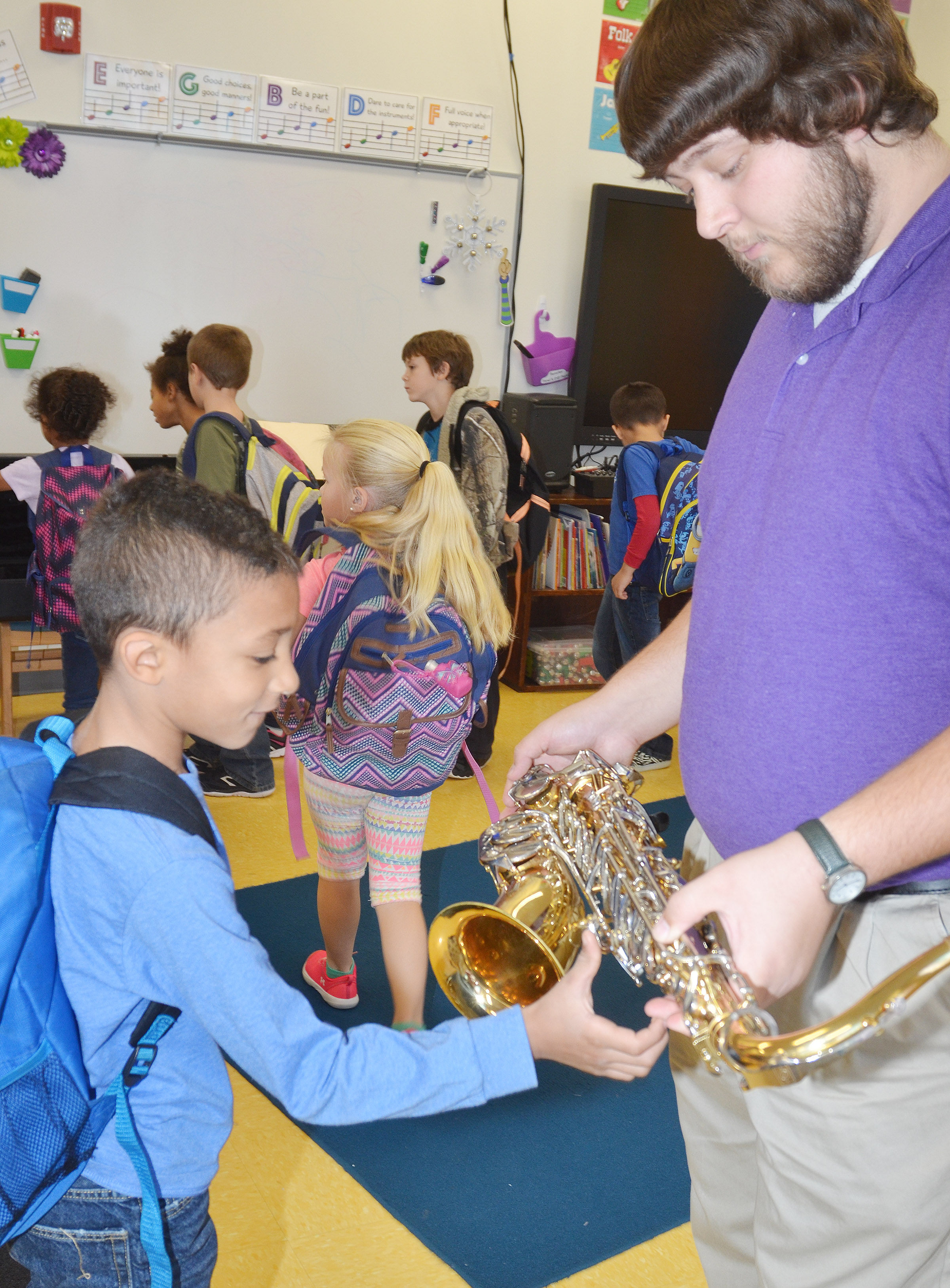 CES first-grader Elijah Williams touches Campbellsville University education student Scott Caffee's tenor saxophone.