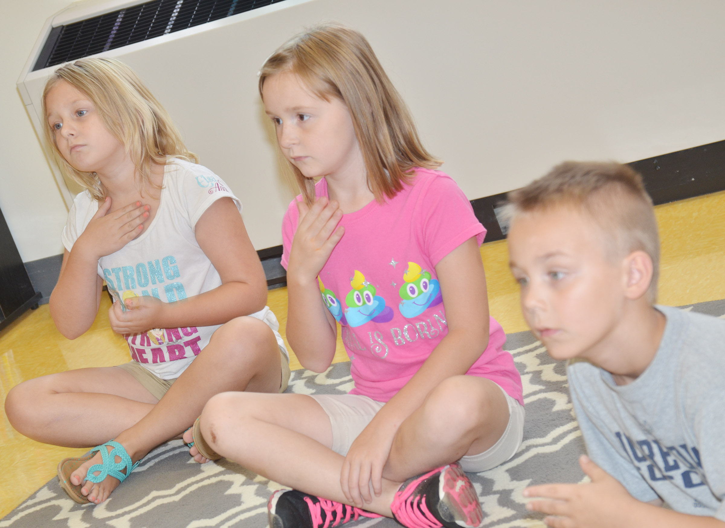 From left, CES second-graders Allison Dean, Gracie Murphy and Hunter Bates keep a steady beat.