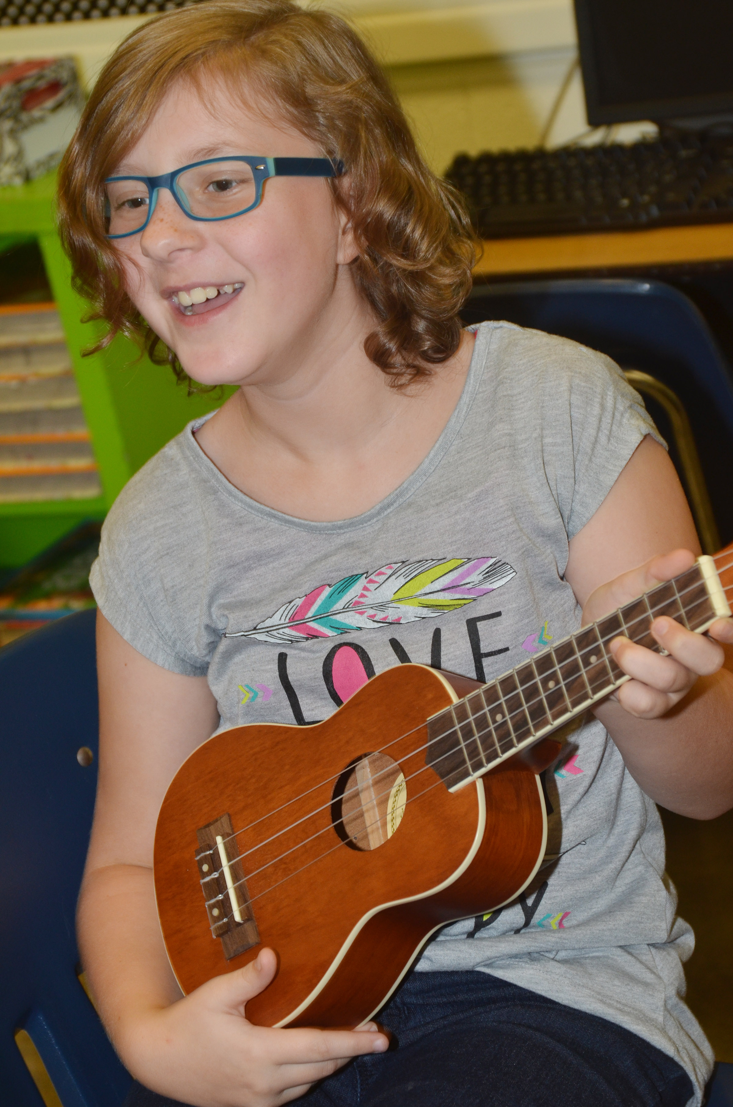 CES fifth-grader Bryanna Fitzgerald laughs as she plays the ukulele.