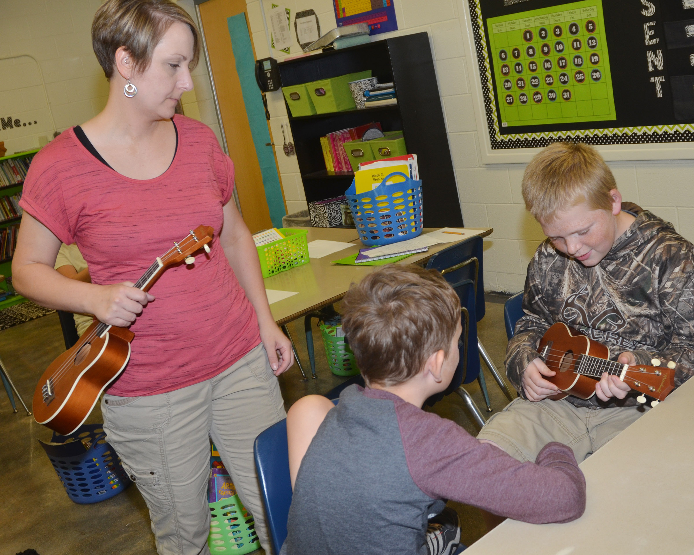 CES music teacher Jessica Floyd teaches fifth-graders Noah Leachman, at left, and Simon Wilkerson how to play a chord.