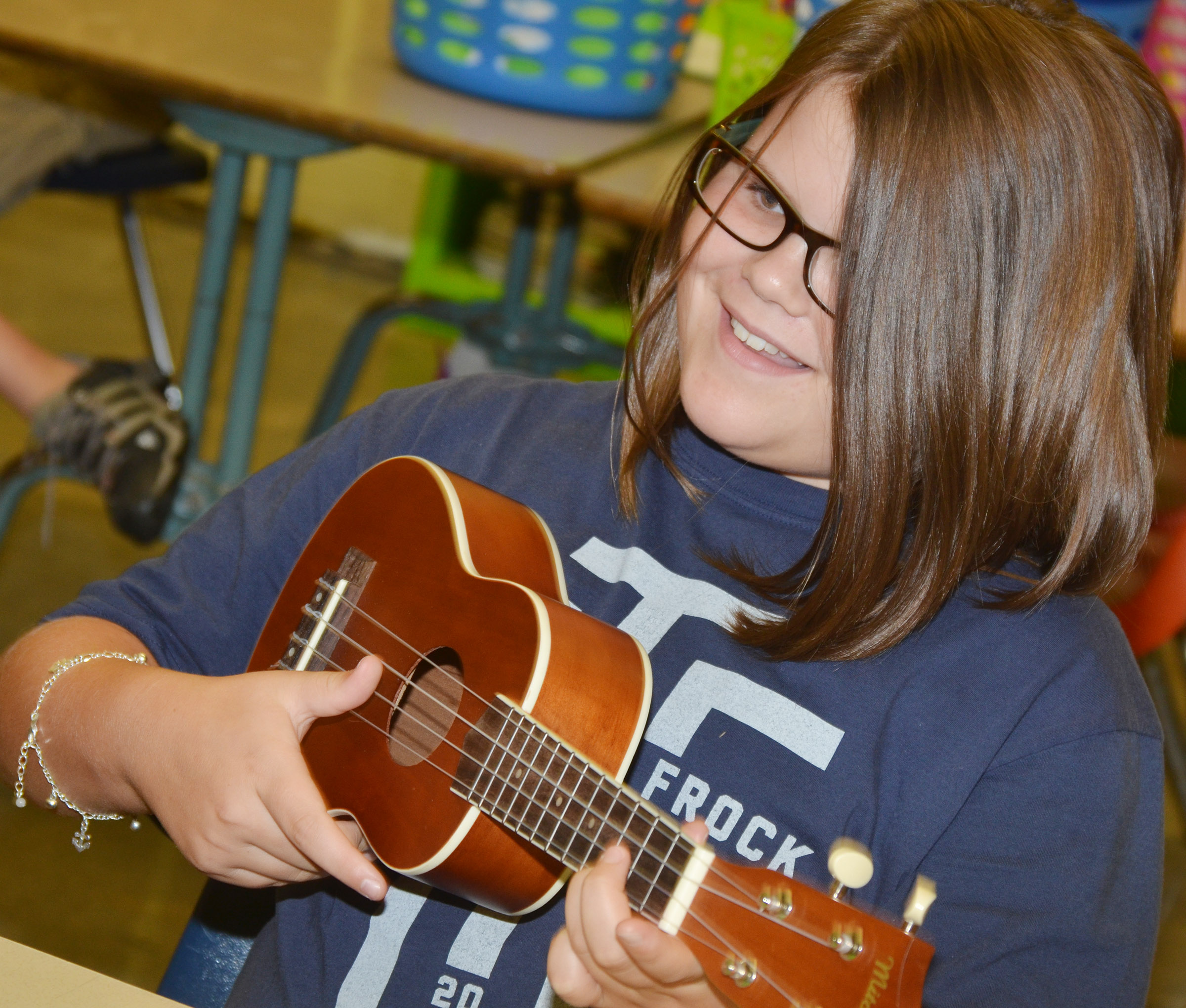 CES fifth-grader Keeley Dicken strums a note.