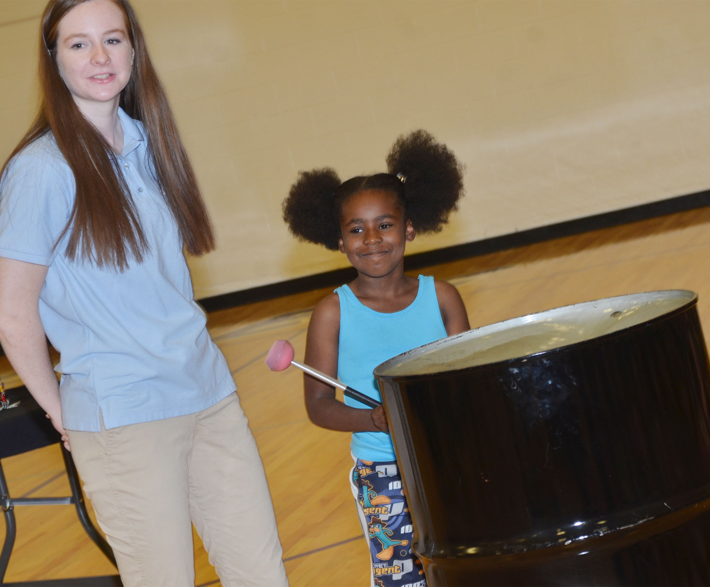 CES first-grader Destini Gholston plays the steel drum, with help from CU Steel Band member Hayley Rockwell.