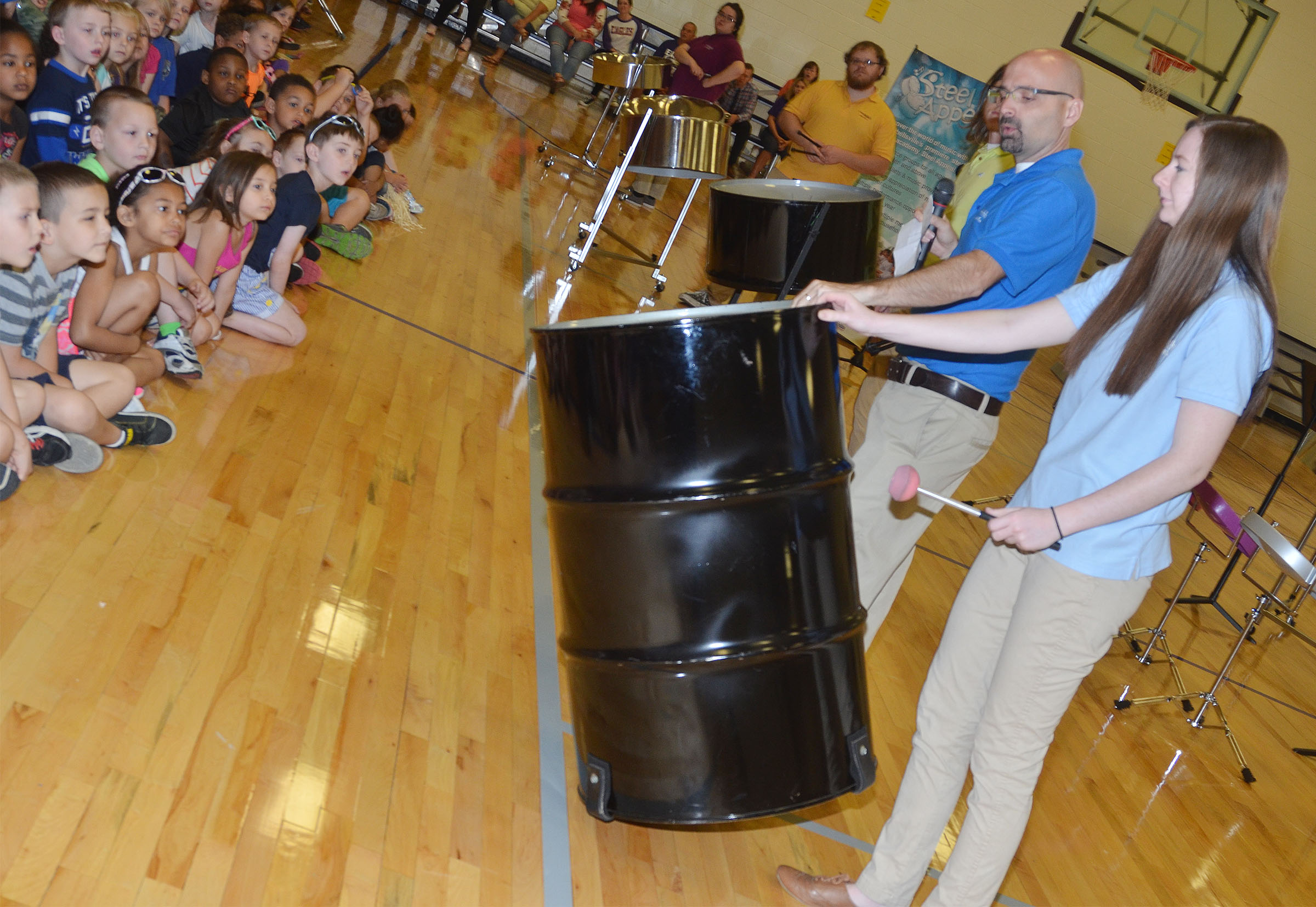 CU Steel Band Director Dr. Chad Floyd, associate professor of percussion, and Steel Band member Hayley Rockwell show CES students a steel drum.