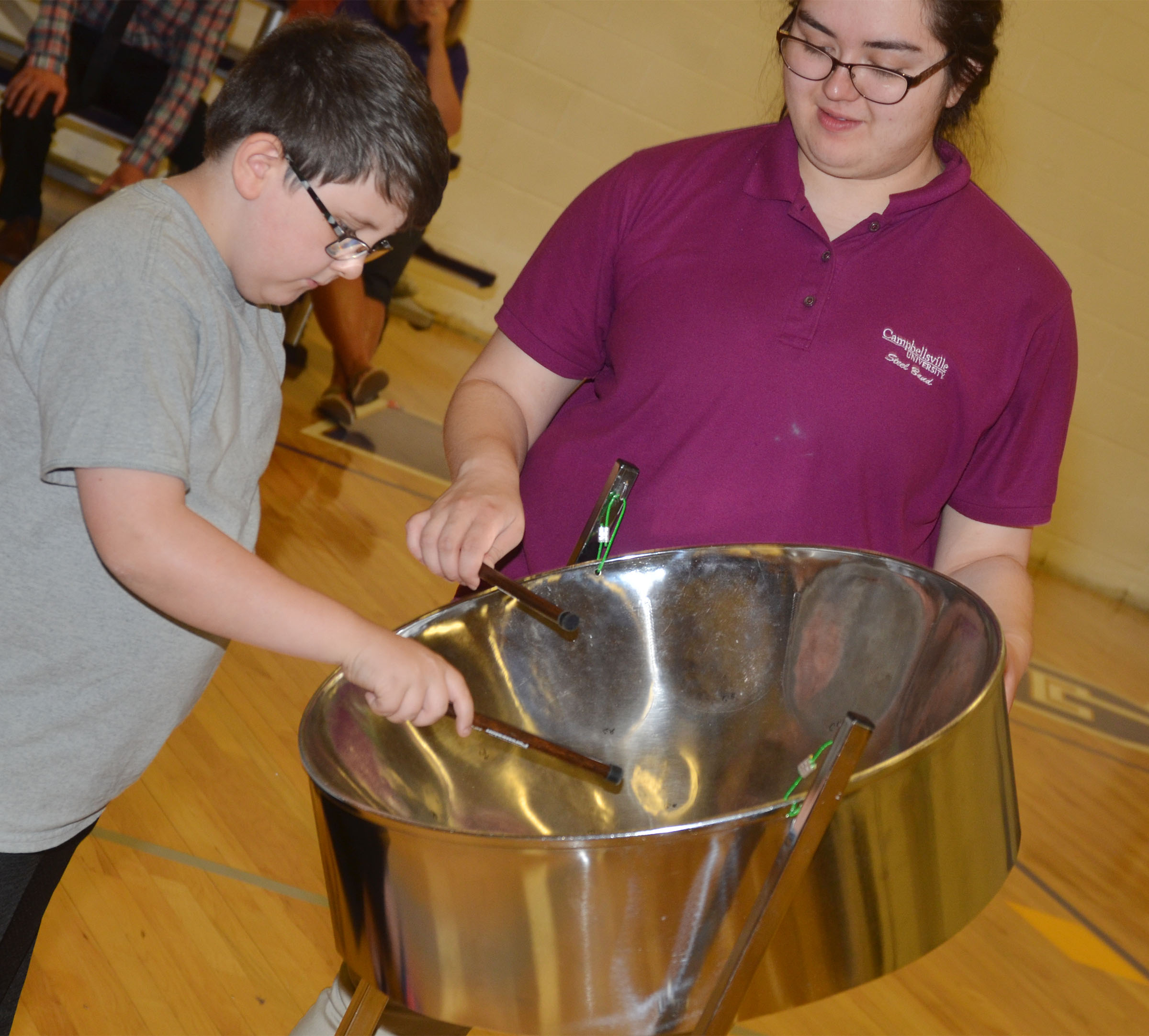 CES second-grader Mason Jackson plays the steel drum, with help from CU Steel Band member Tiffany Riggins.