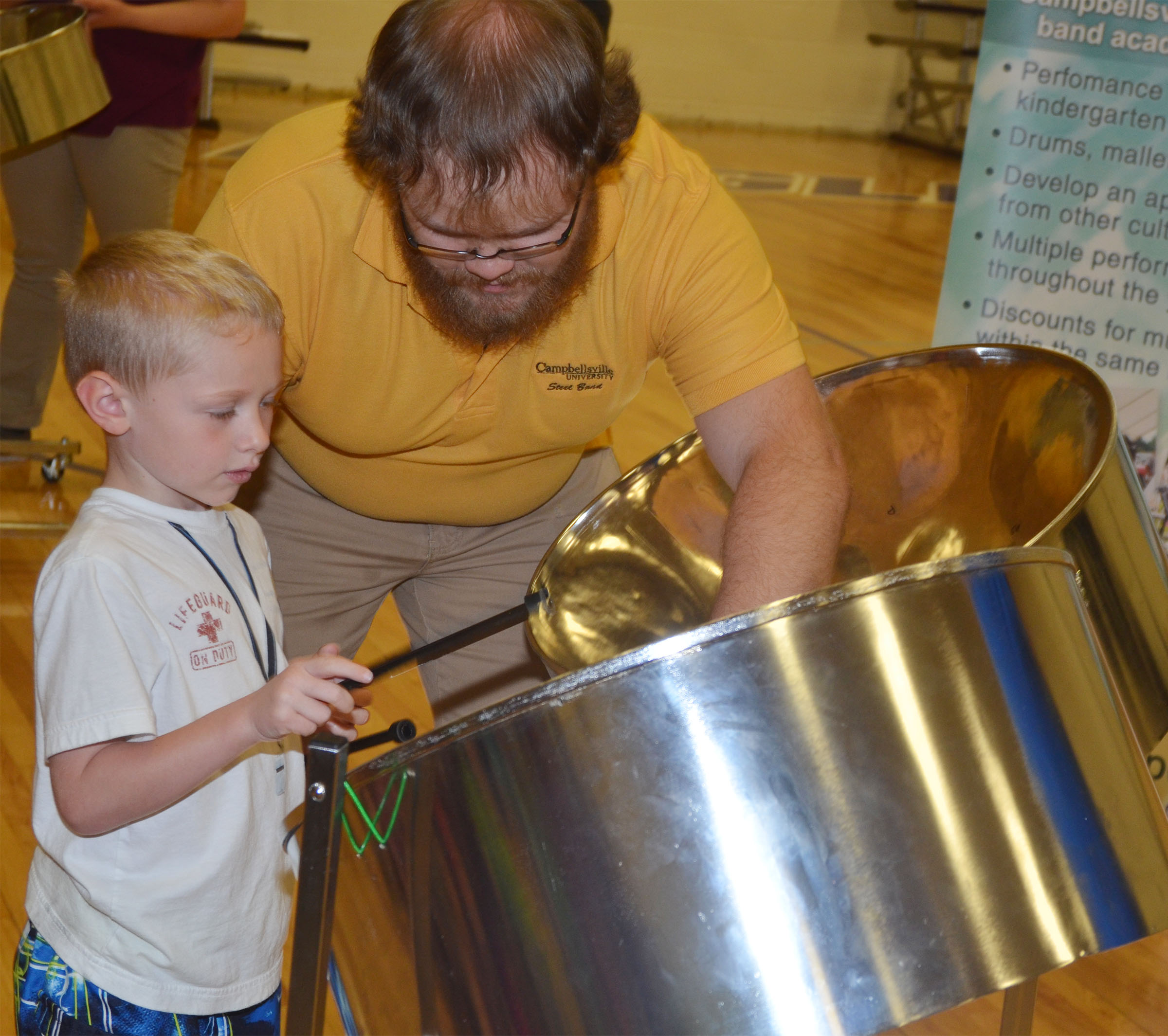 CES kindergartener Jackson Wright plays the steel drum, with help from CU Steel Band member Chris Blakley.