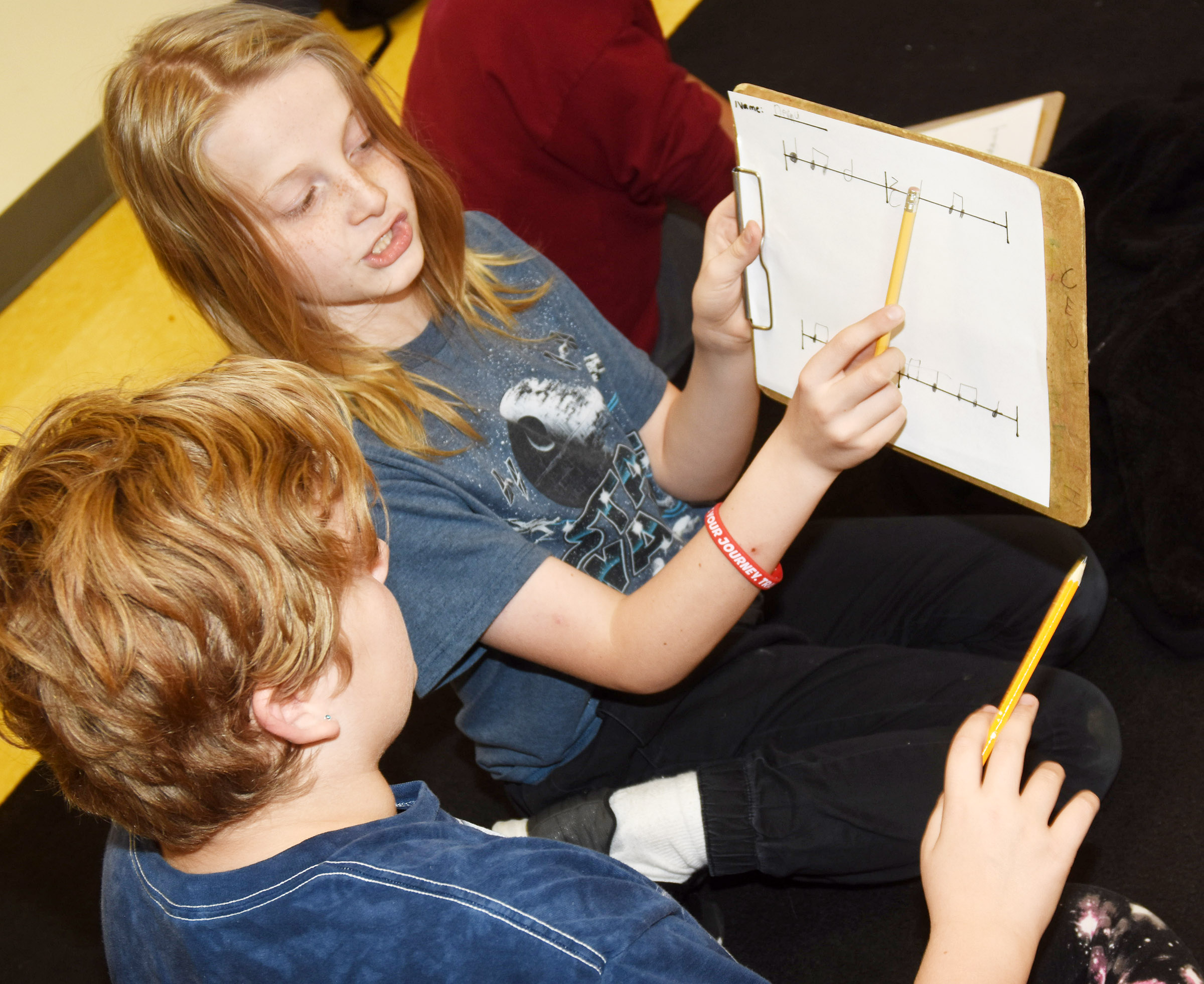 CES fifth-grader Devin Underwood, at right, helps classmate Arianna Childers as she writes her rhythms.