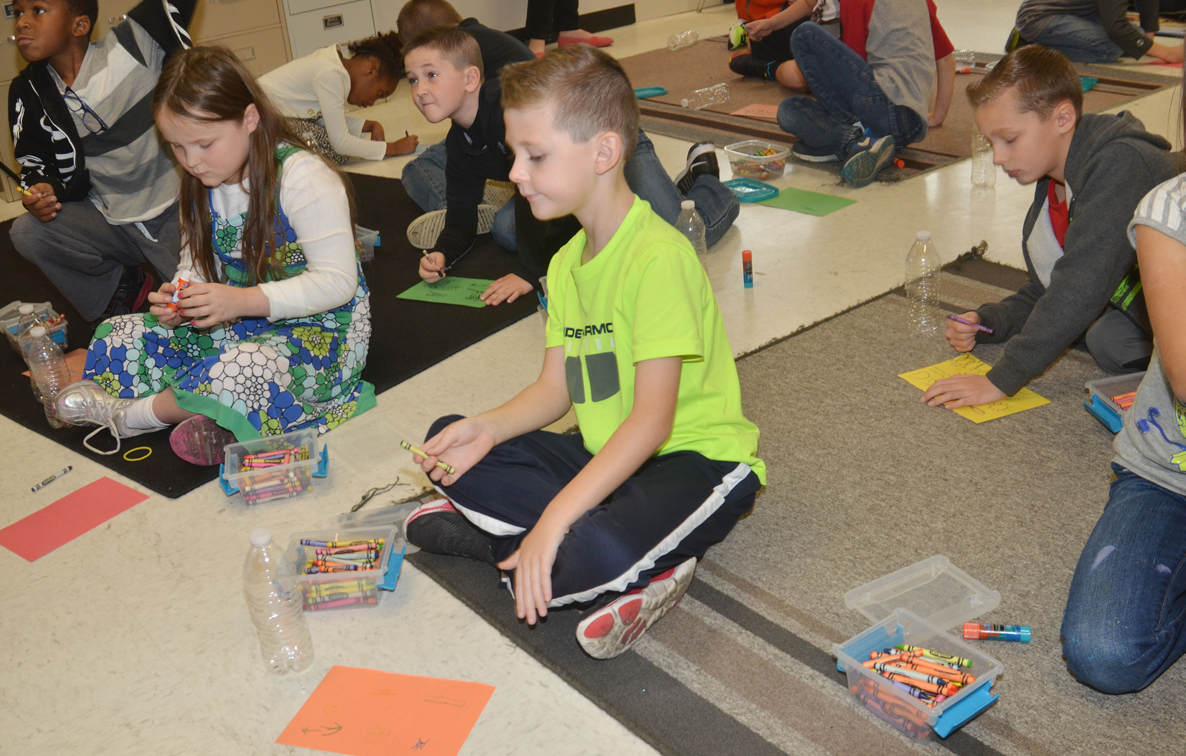 CES second-graders work on decorating their construction paper, which will be glued to their water bottle and made into Native American instruments.