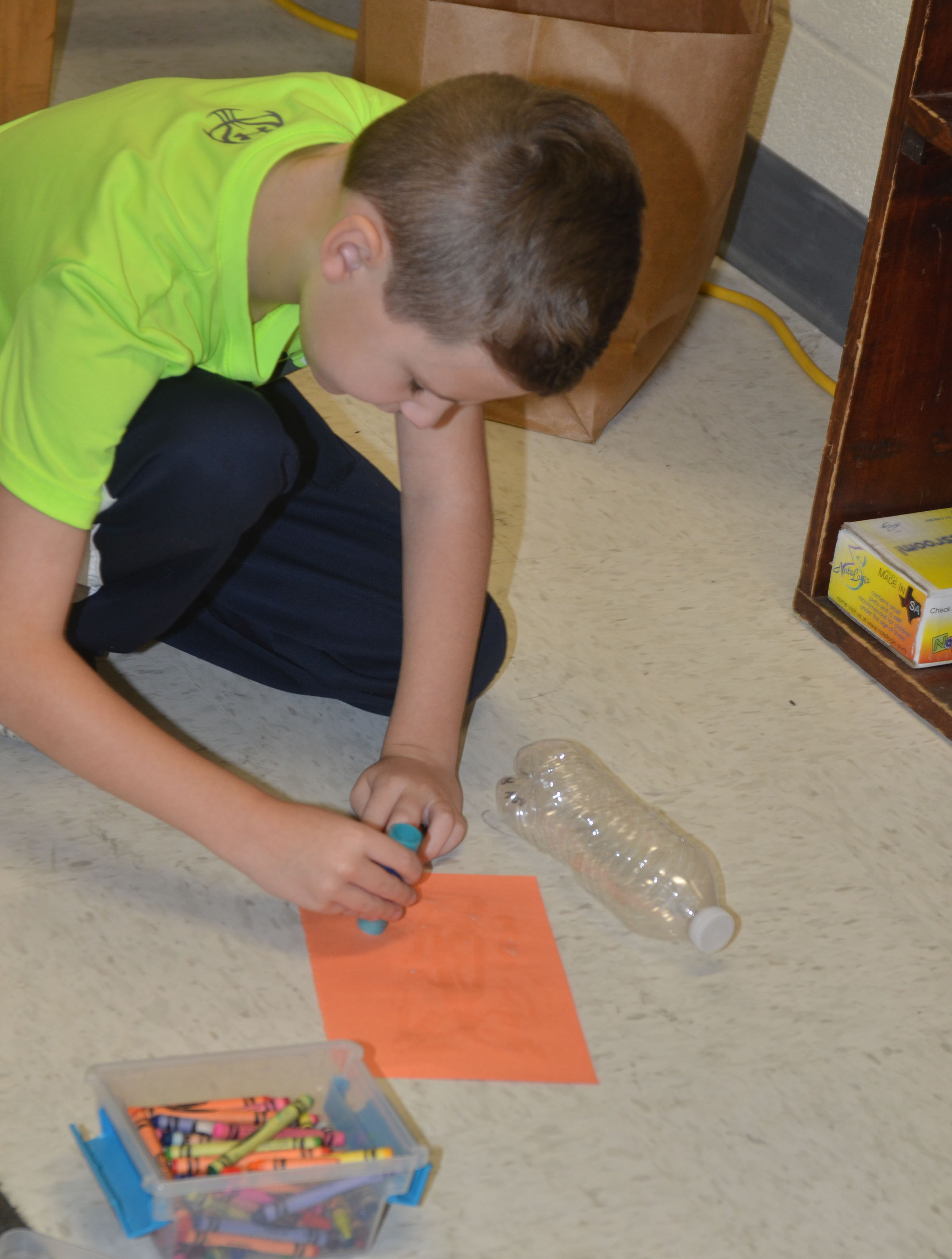 CES second-grader Ryan Tungate glues his construction paper to his water bottle to make his Native American instrument.