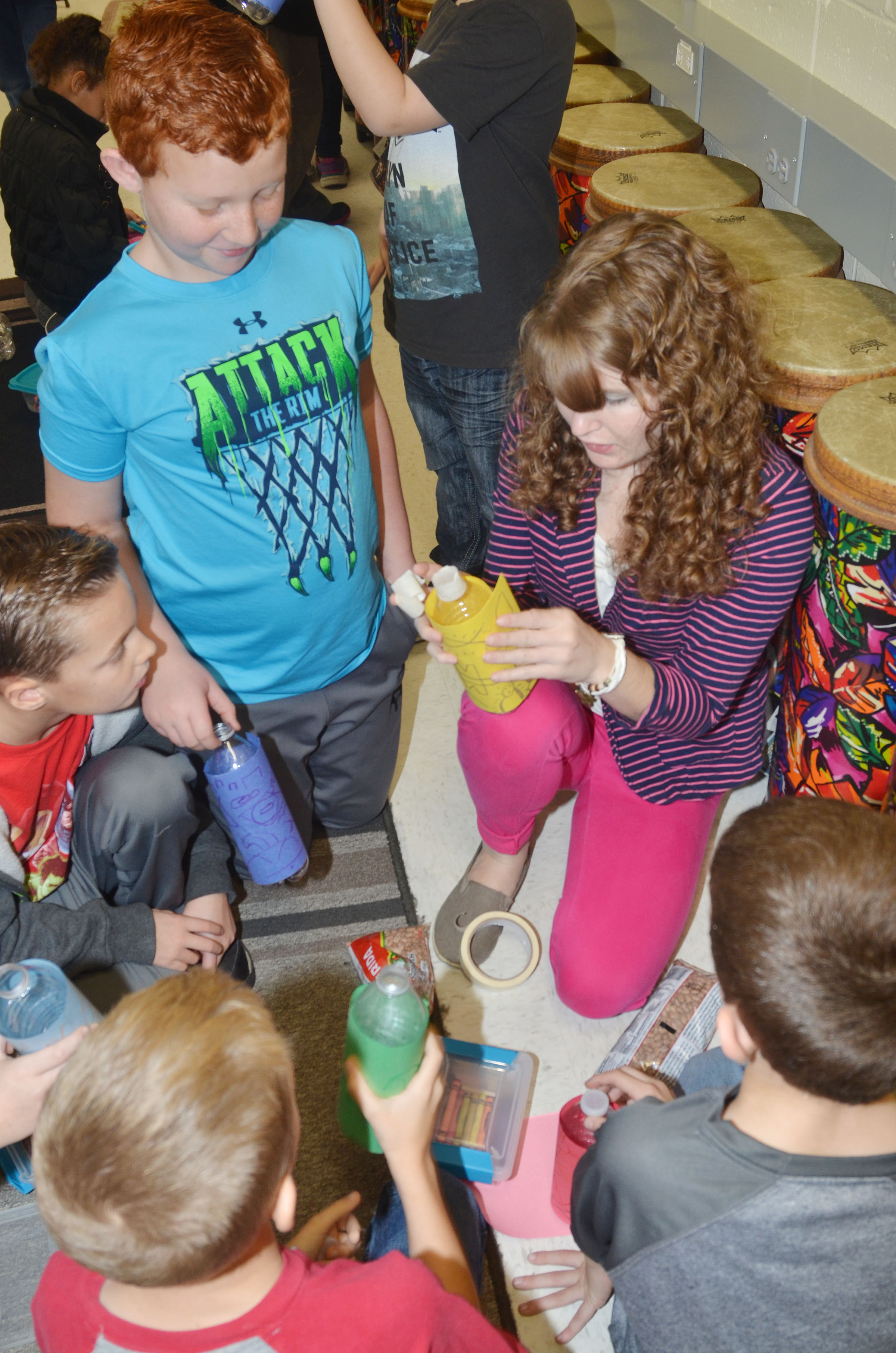 Campbellsville University music education student Carolyn Meador – who did her student teaching at CES with music teacher Cyndi Chadwick – helps second-grader Reece Swafford and his classmates glue their construction paper to their water bottles.