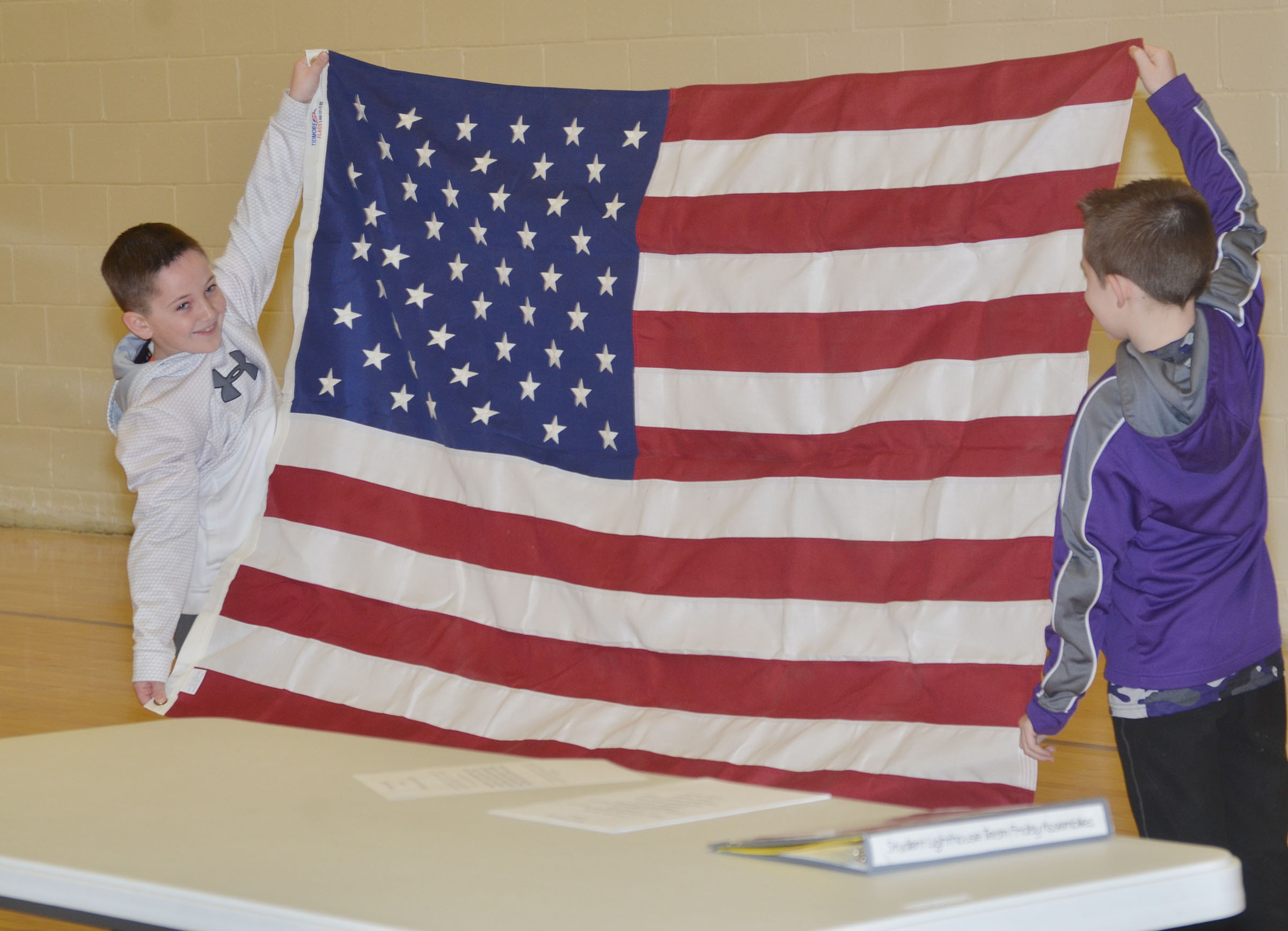 CES second-graders Luke Adkins, at left, and Lanigan Price hold the American flag as CES students say the Pledge of Allegiance.