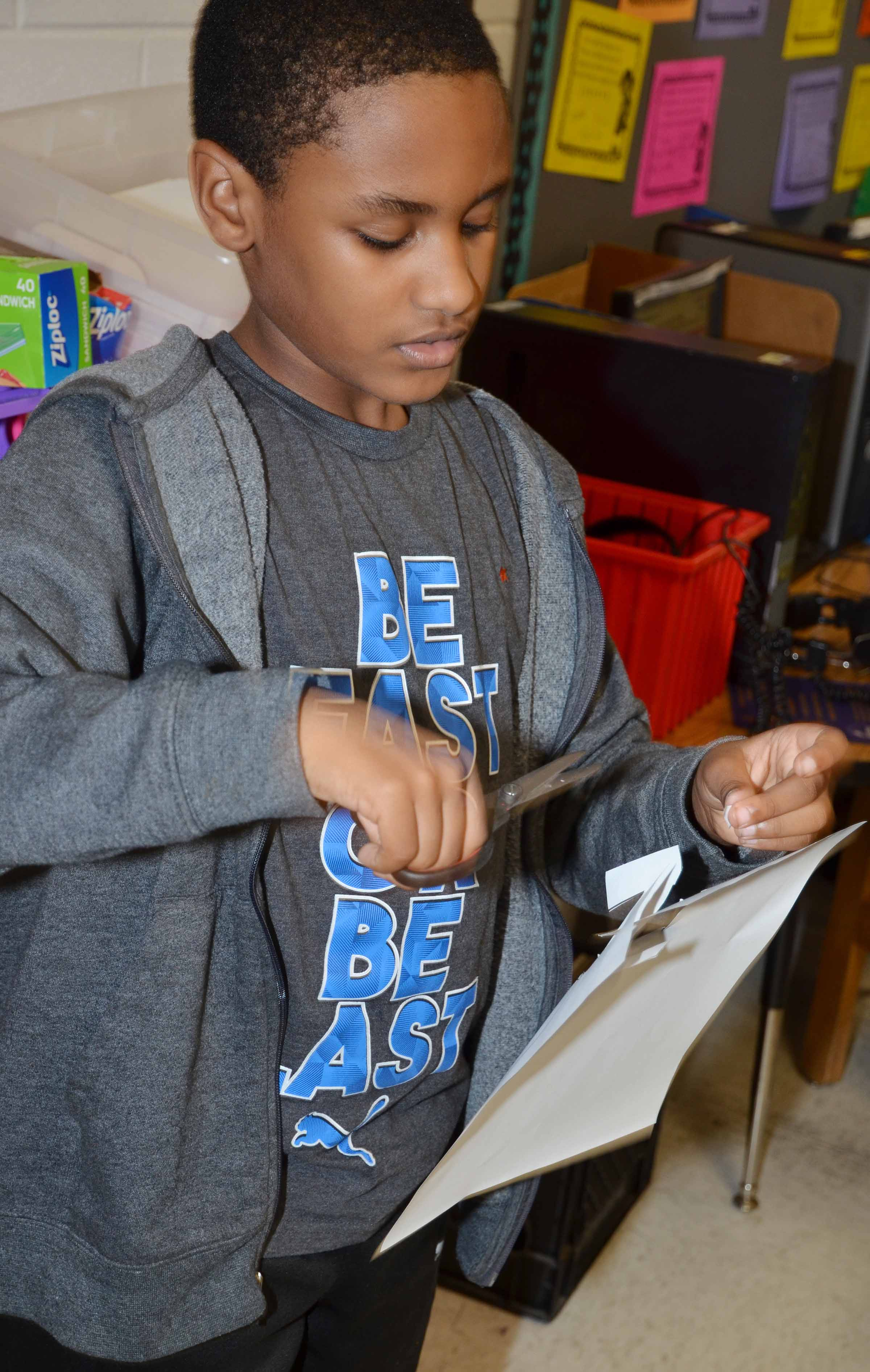 CES third-grader Shaiden Calhoun cuts out his New Year's resolution.