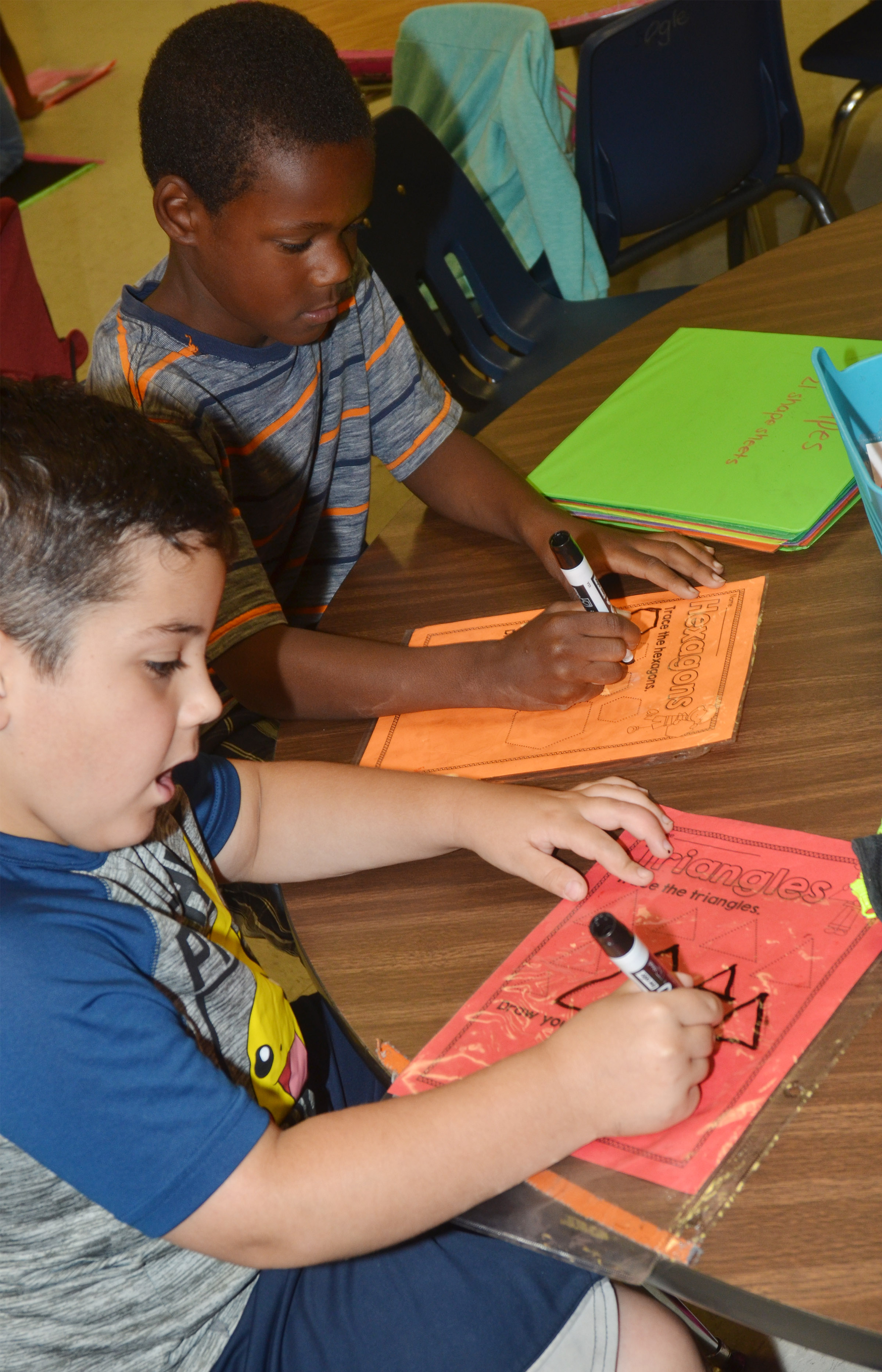 CES first-graders Nicholas Almeida, in front, and Lazarick Miller draw shapes.