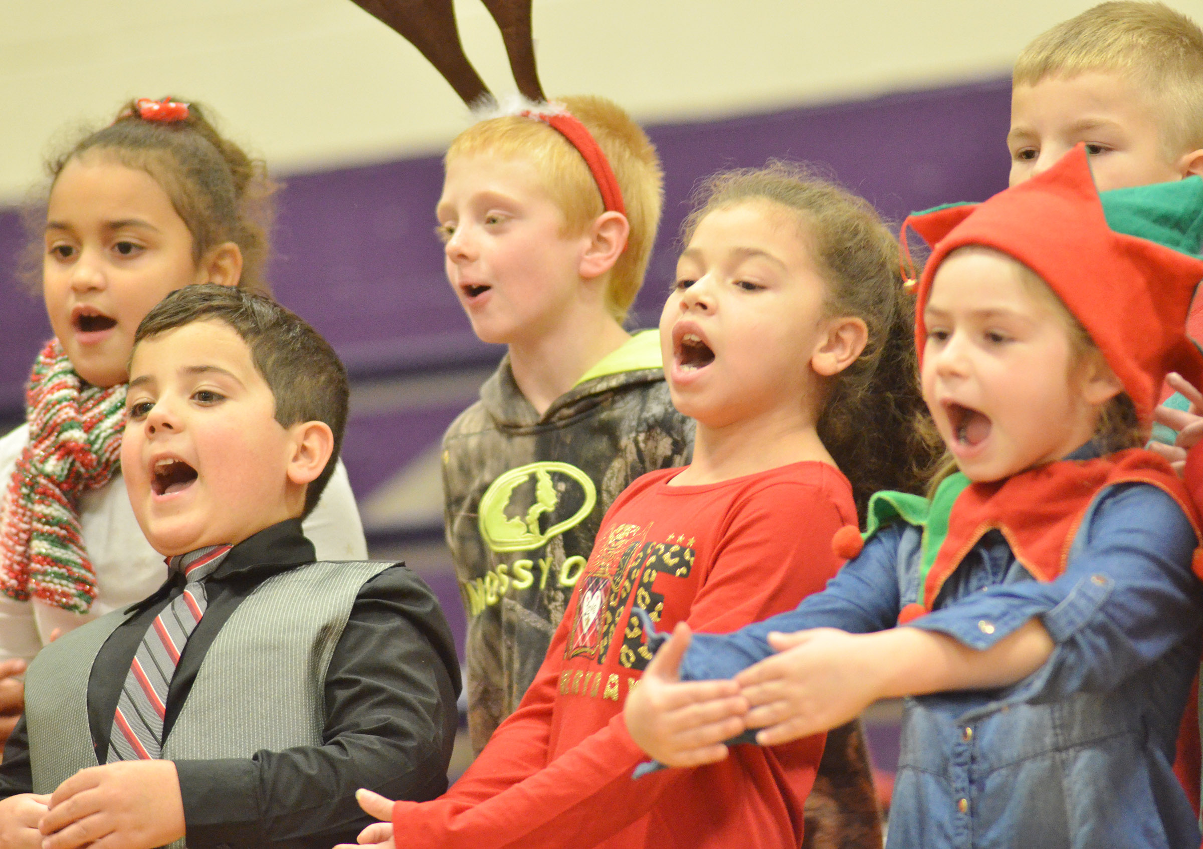 From left, front, CES first-graders Nicholas Almeida, Ammarissa Nunez and Lainey Price sing about Santa Claus.