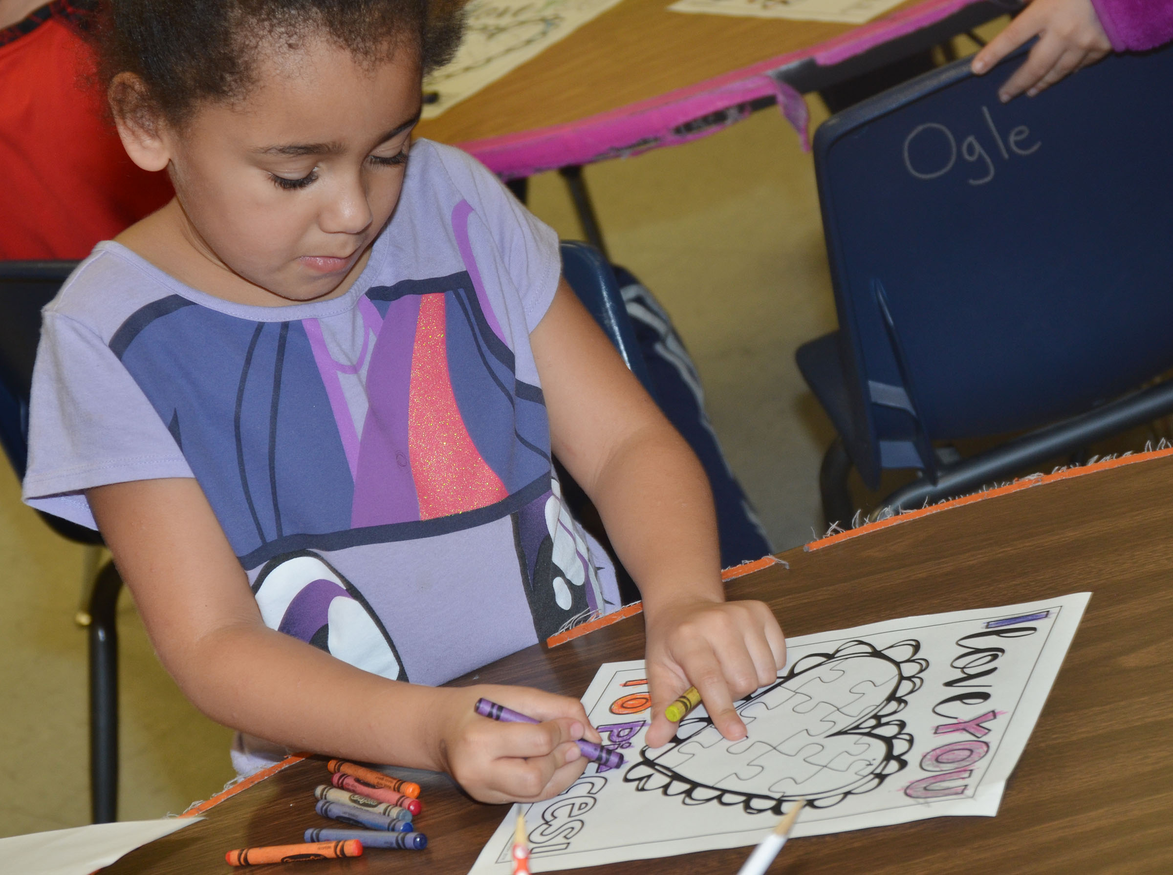 CES first-grader Keitona Whitehead colors a heart.