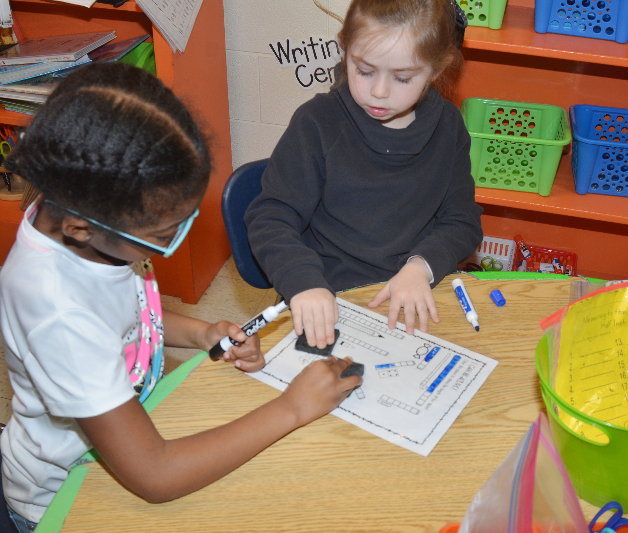 CES first-graders Willow Griffin, at left, and Lainey Price practice addition by playing a math measurement game.