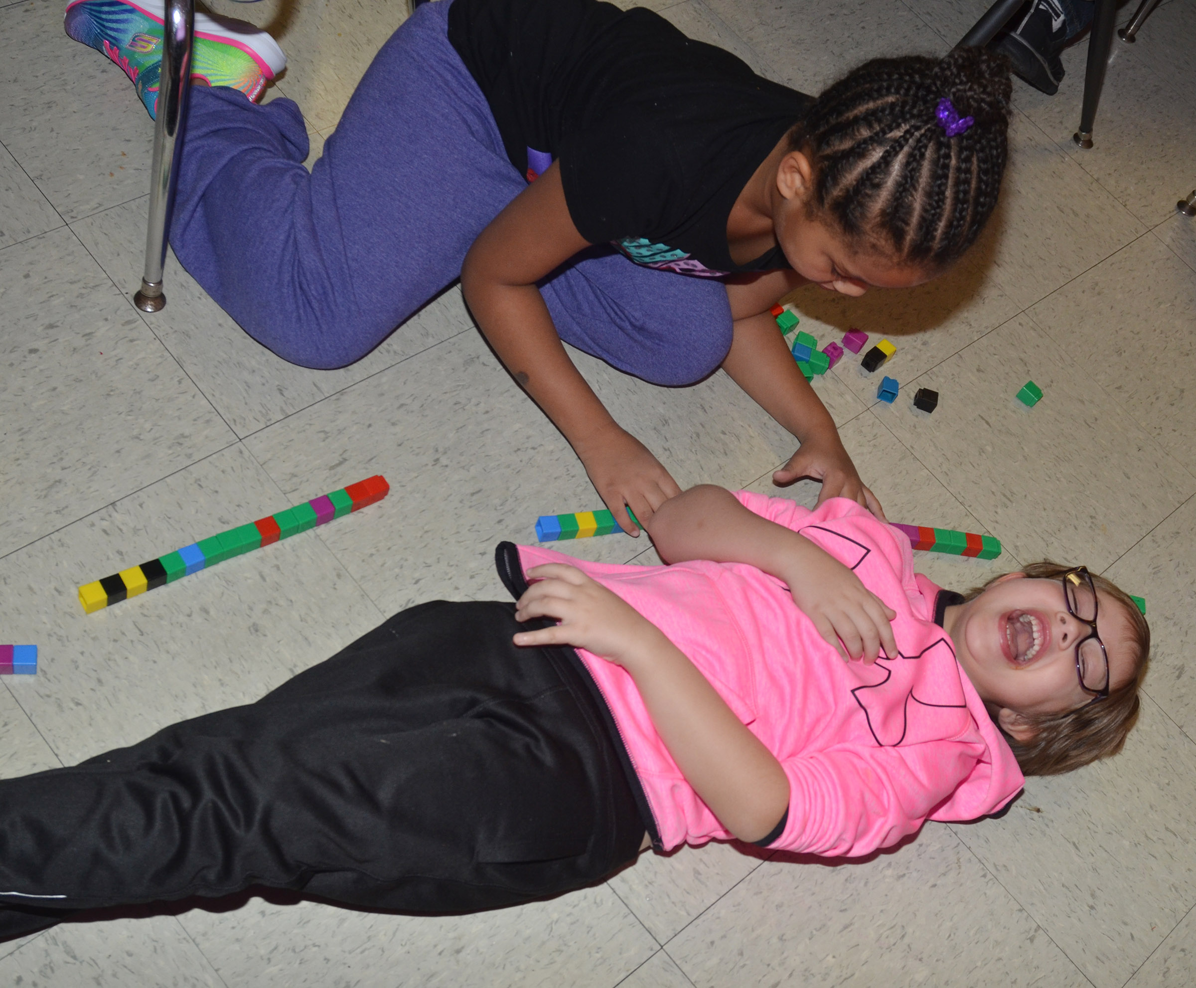 CES first-grader Addelyn Dooley laughs as Journey Webb counts her height in blocks.