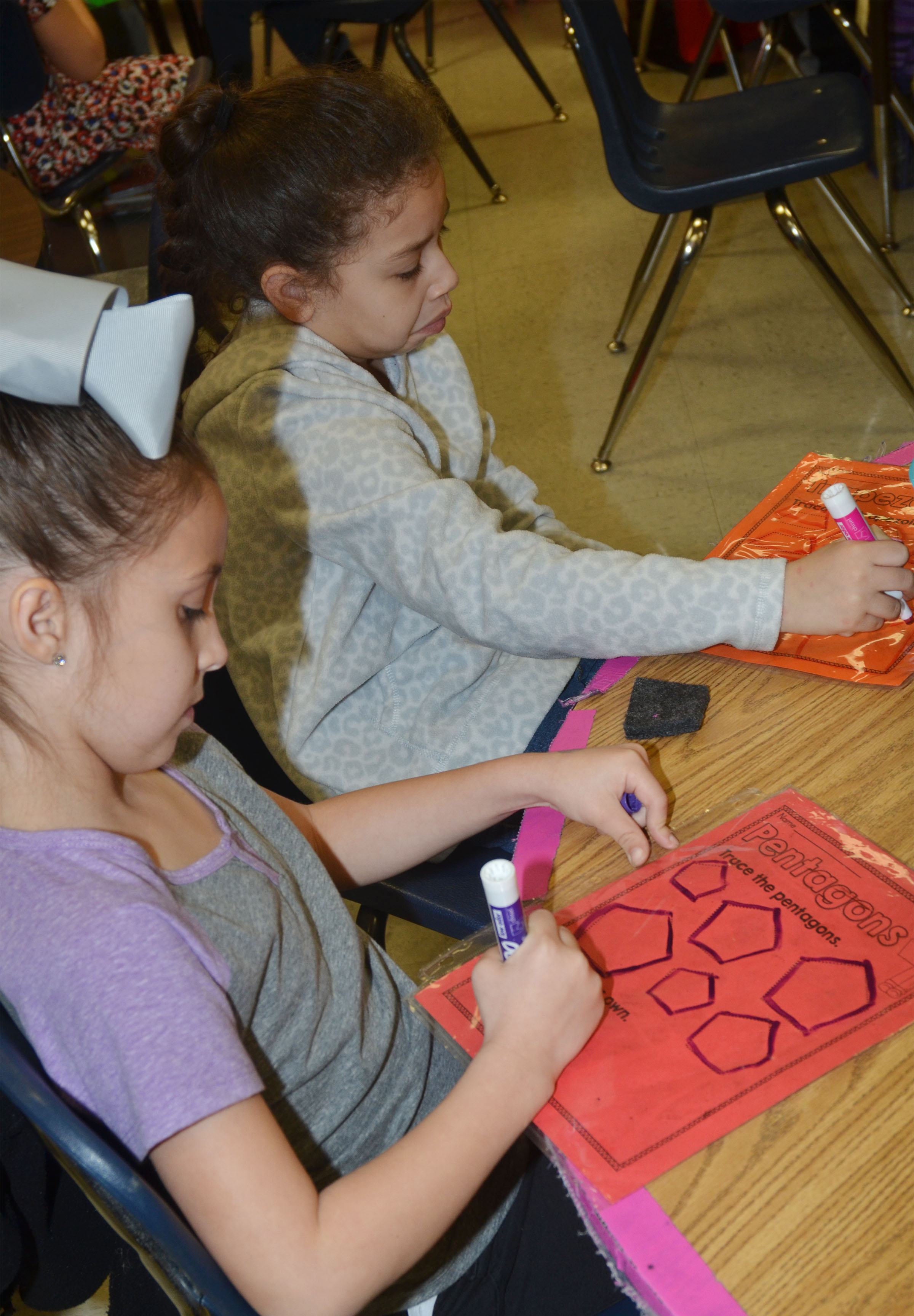 CES first-graders Lillian Martin, at left, and Ammarissa Nunez trace pentagons and trapezoids.