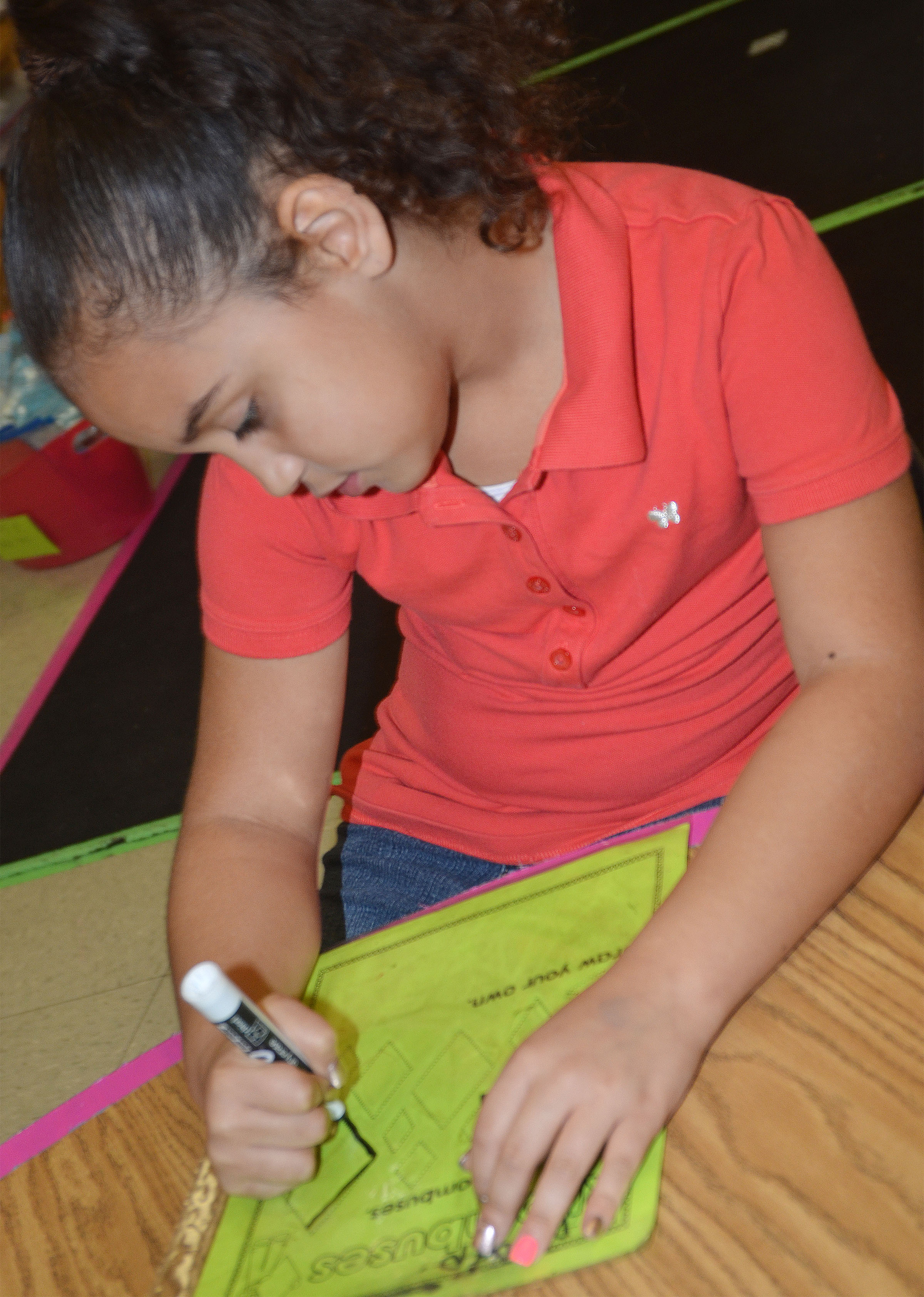 CES first-grader Maleigha Travis traces a rhombus.