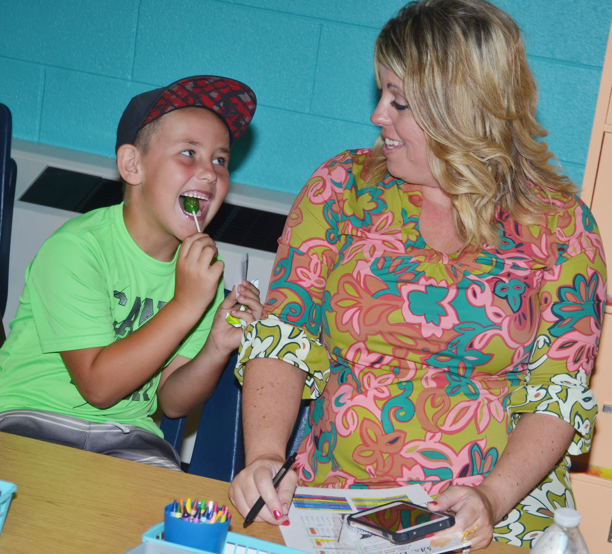 CES Principal Elisha Rhodes registers her son Braxton, a first-grader, for his classes.