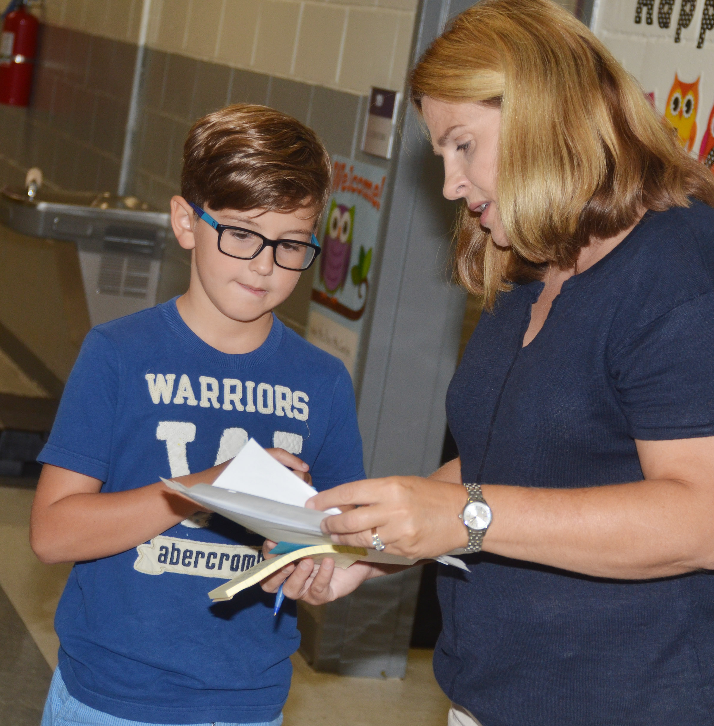CES Guidance Counselor Sonya Orberson asks third-grader Tye Rhodes to help her collect some paperwork.