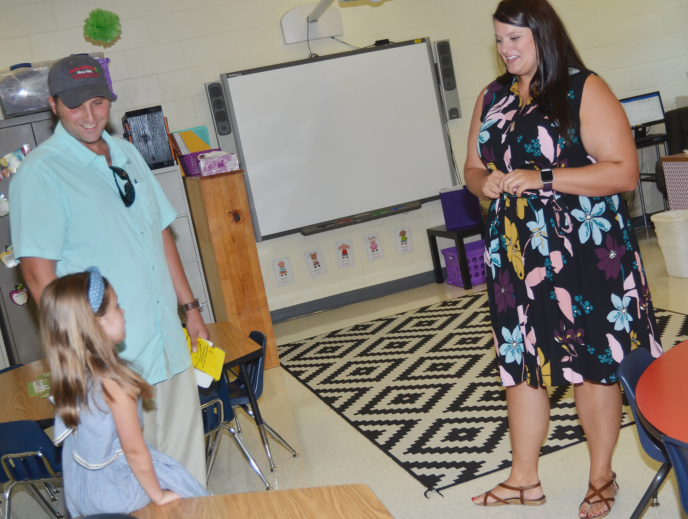 CES first-grade teacher Miriah Cox talks to student Delaney Staton and her step-father, Adam Reynolds, about the new school year.