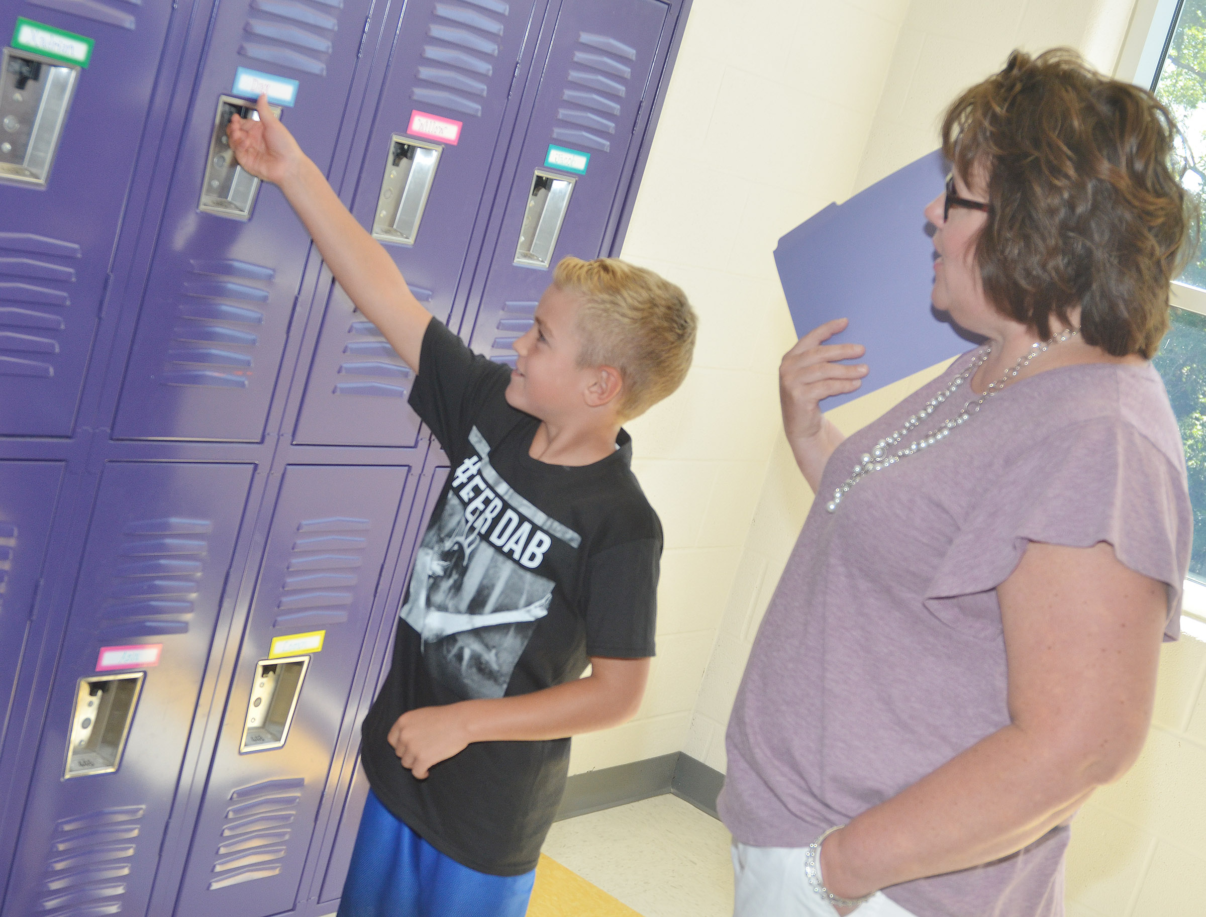 CES second-grade teacher Tracey Rinehart helps student Dax Gray find his locker.