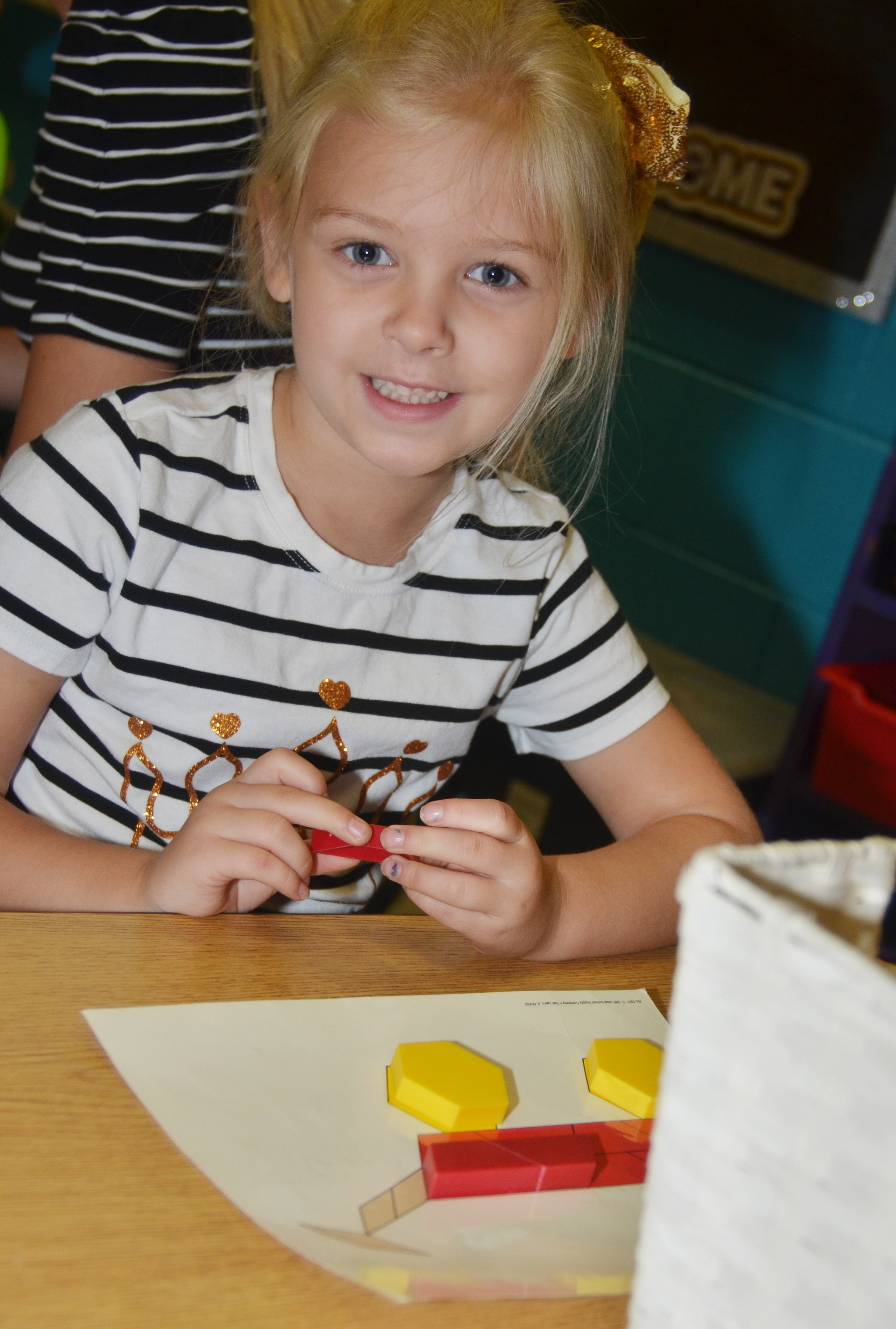 CES first-grader Aubrey Novak smiles as she works a shape puzzle.