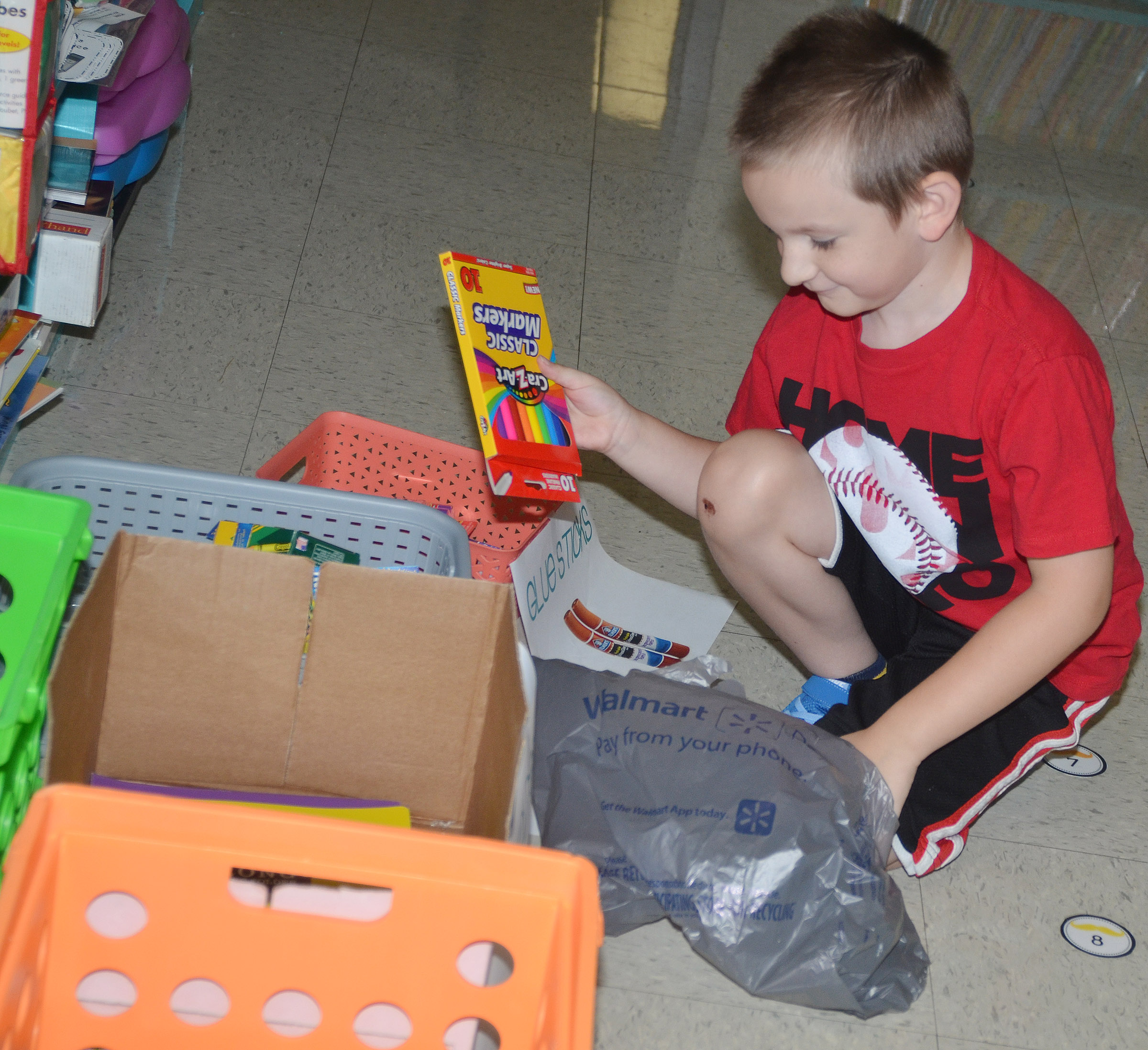 CES first-grader Ryne Gumm sorts his school supplies in his classroom.