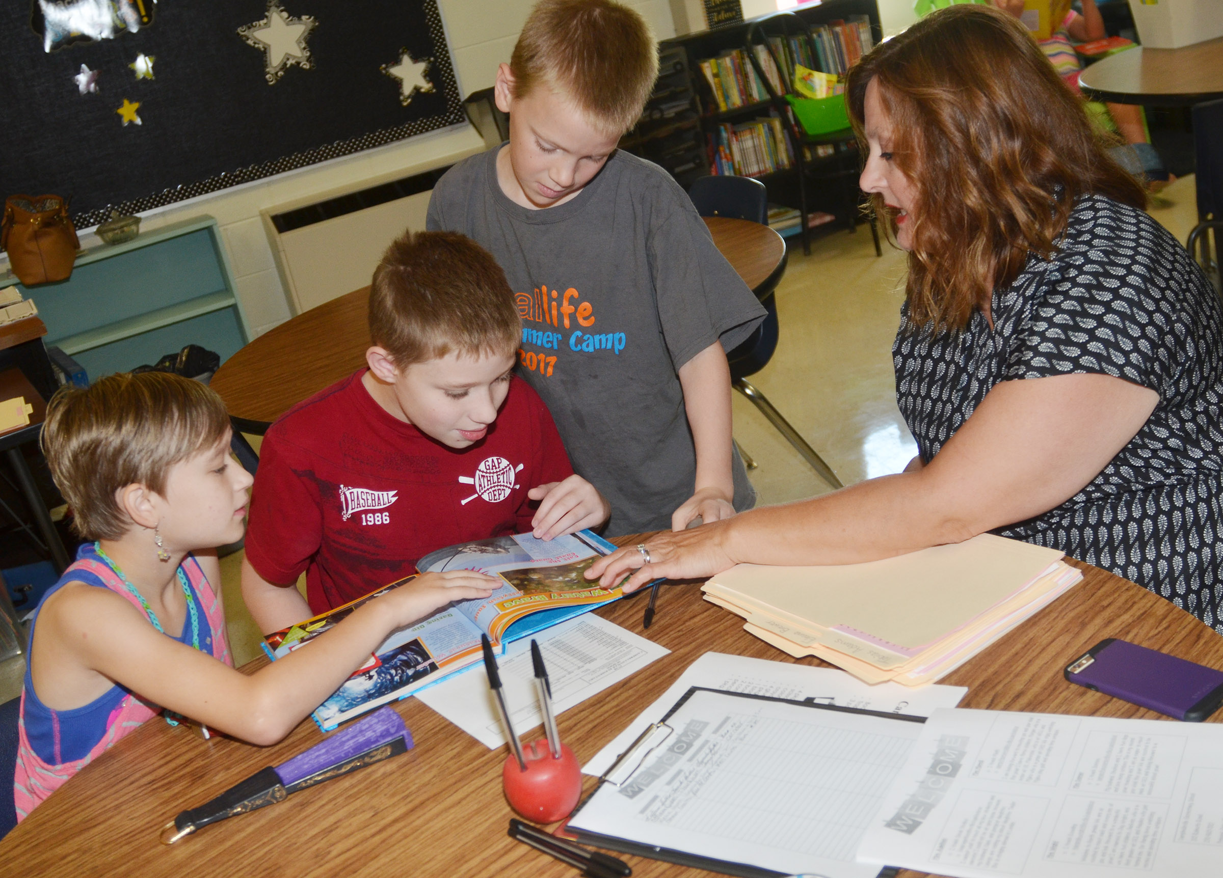 CES fourth-grade teacher Garnetta Murrell reads with, from left, fourth-grader Katie Nunn, Campbellsville Middle School sixth-grader Willie Nunn and fourth-grader Connor Coots.