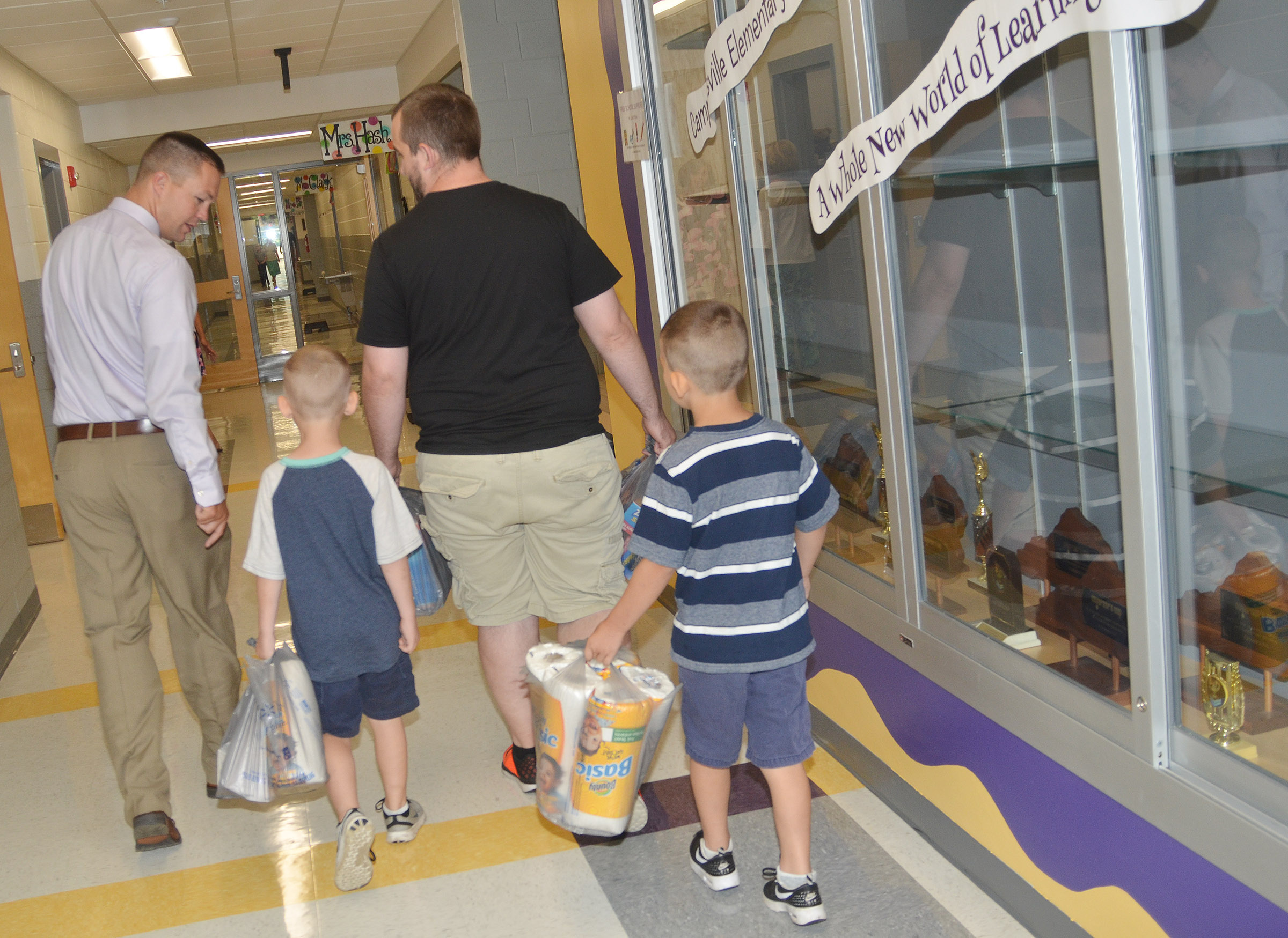 CES Assistant Principal Weston Jones, at left, leads CES students and their father to their classroom.