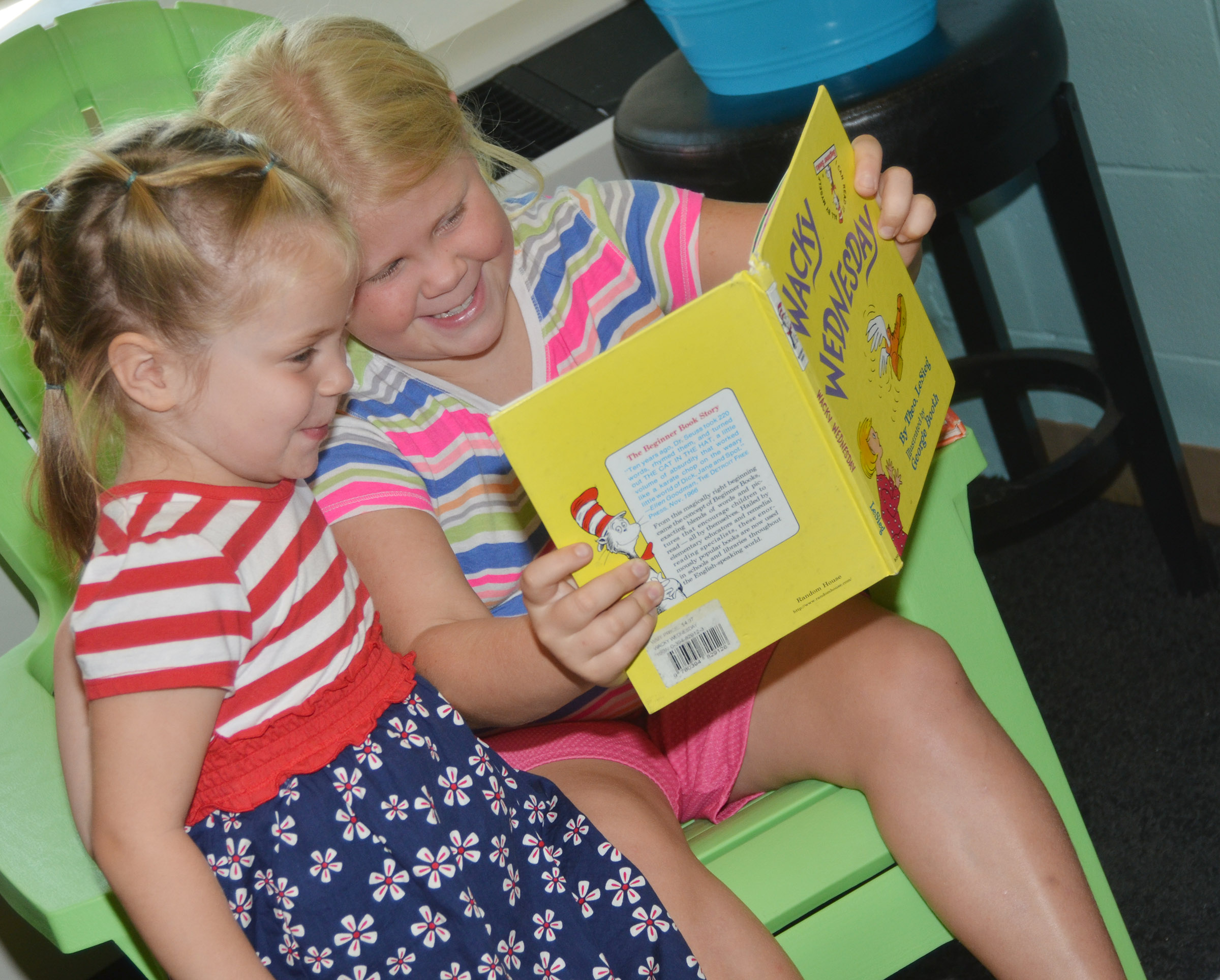 CES fourth-grader Lily Coots reads to her sister, Charlotte, who will attend preschool at CES this year.