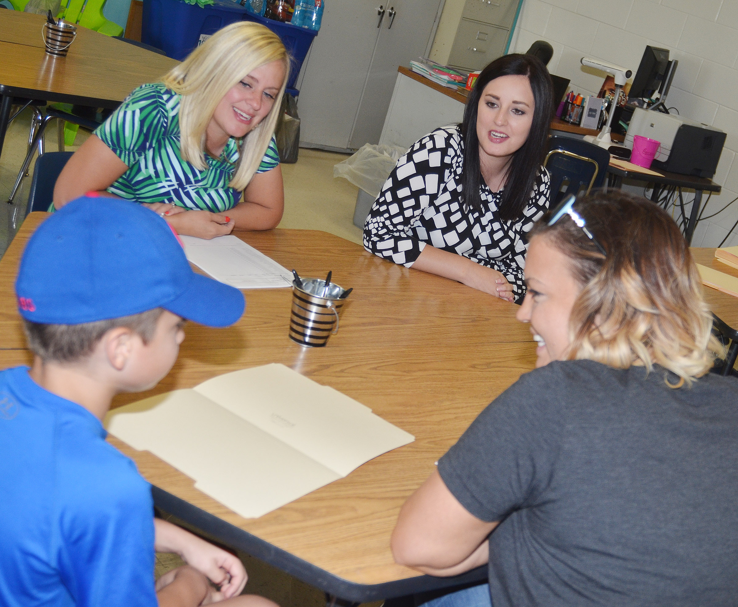CES fourth-grade teachers Maranda Wright, at left, and Samantha Coomer talk to student Carson Mills about his classes.