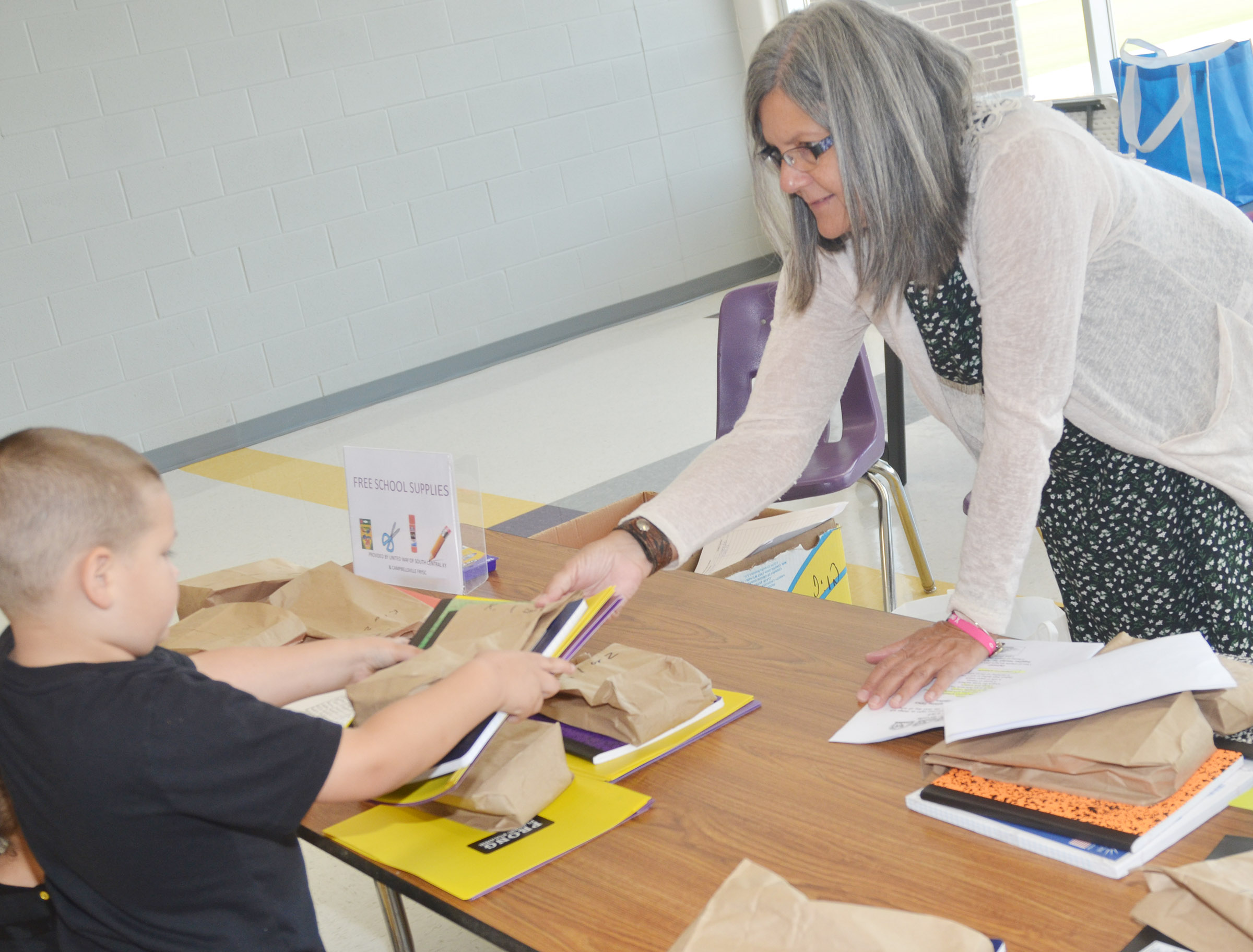 Campbellsville Family Resource and Youth Services Center Director Sue Crabtree passes out free school supplies to CES students.