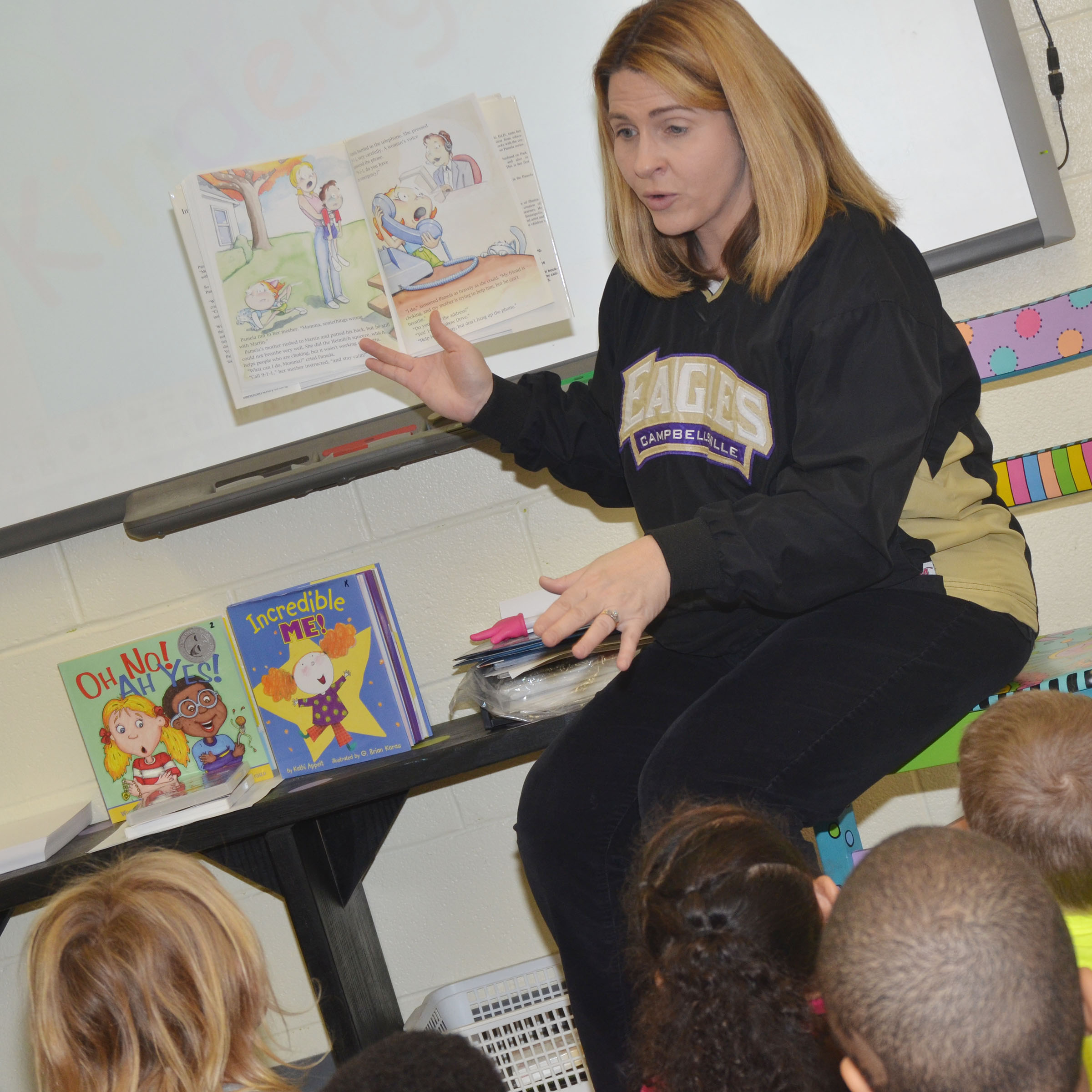 CES Guidance Counselor Sonya Orberson reads to first-graders about how to call 911 in an emergency.