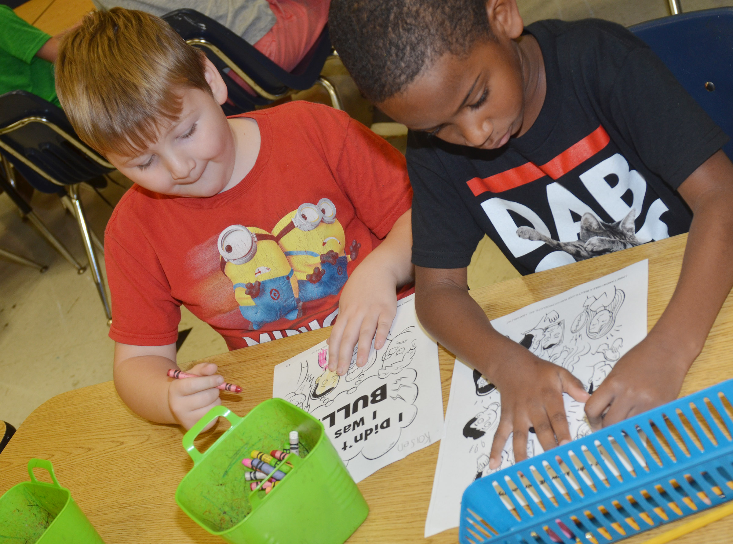 CES first-graders Enrique McDonald, at left, and Kasen Smith color their pages of their class's bullying book.